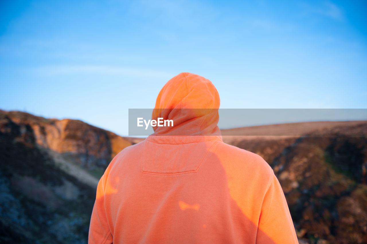 Rear View Of Man Wearing Hood Against Sky