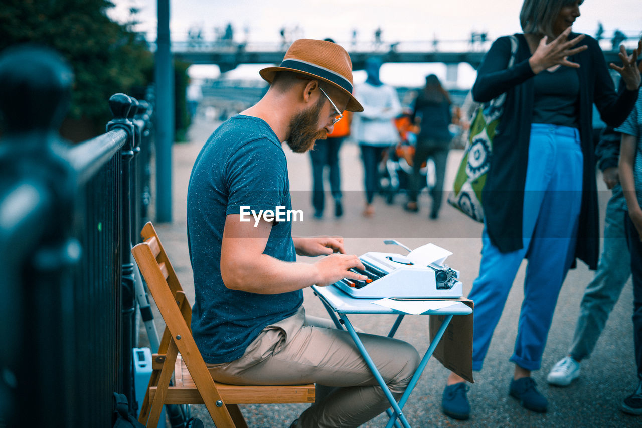 casual clothing, real people, side view, one person, t-shirt, lifestyles, leisure activity, full length, day, outdoors, cap, technology, wireless technology, young adult, city, adult, people