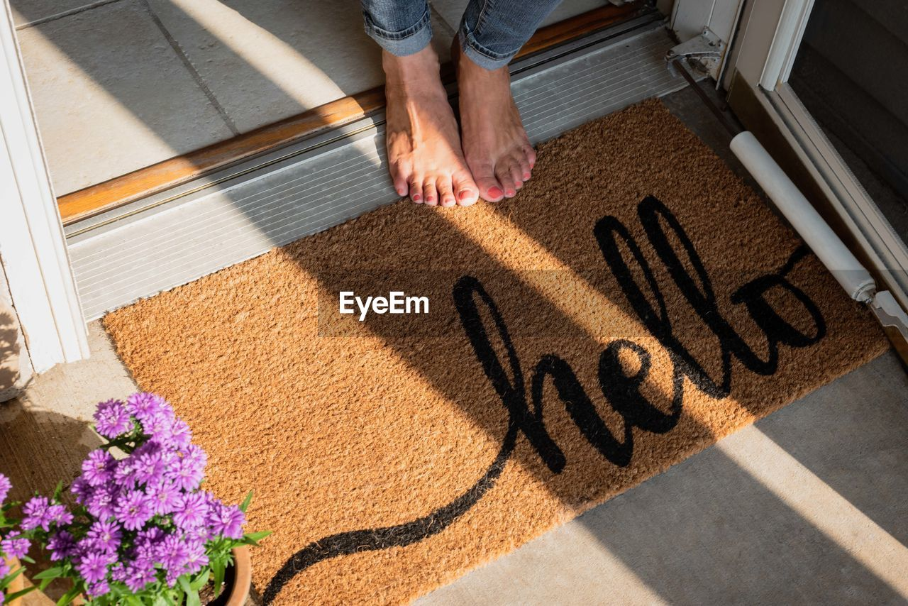 Low Section Of Woman Standing By Doormat With Hello Text