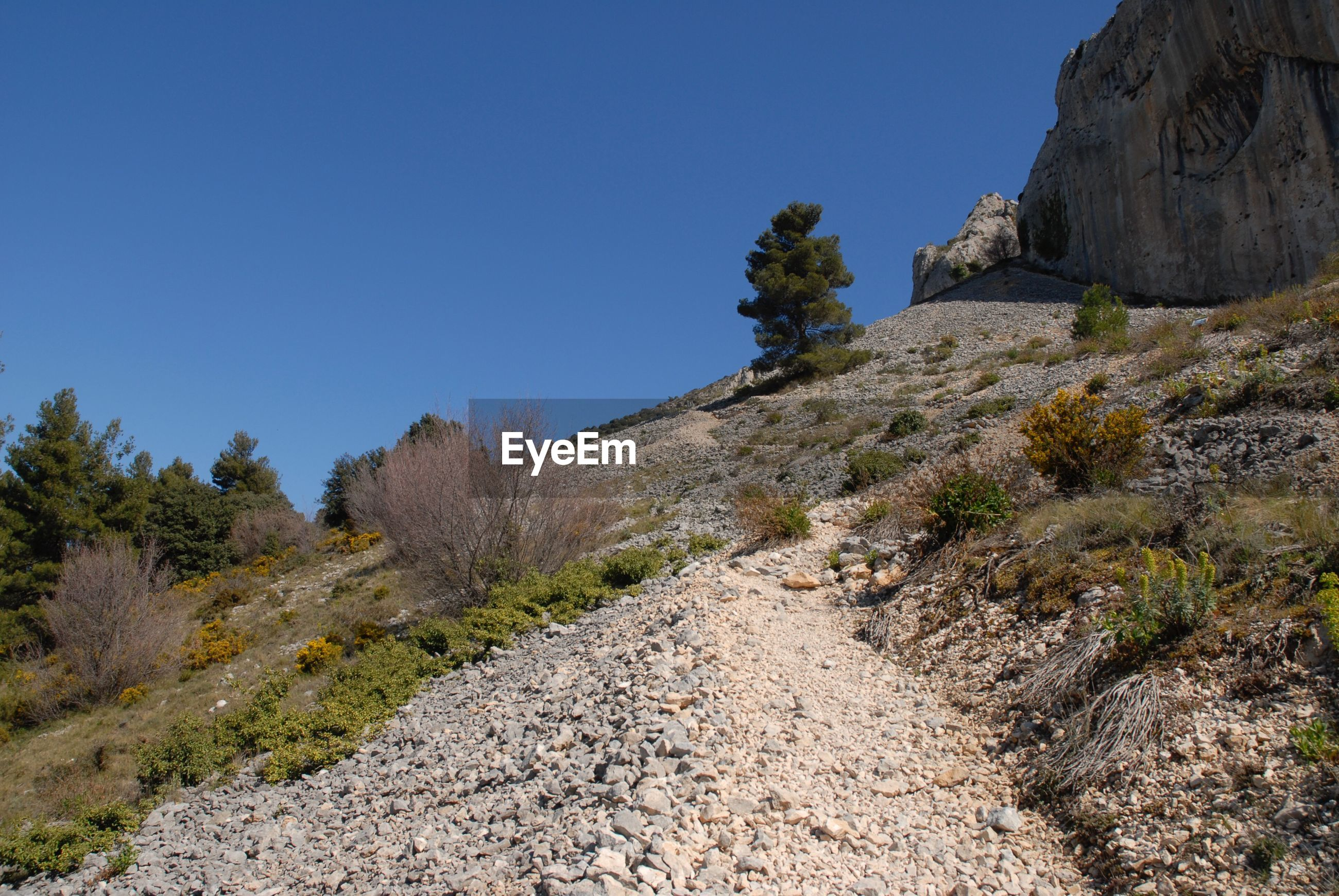 Track over scree slope to el frares limestone rock pinnacles, quatretondeta, sierra serrella, spain