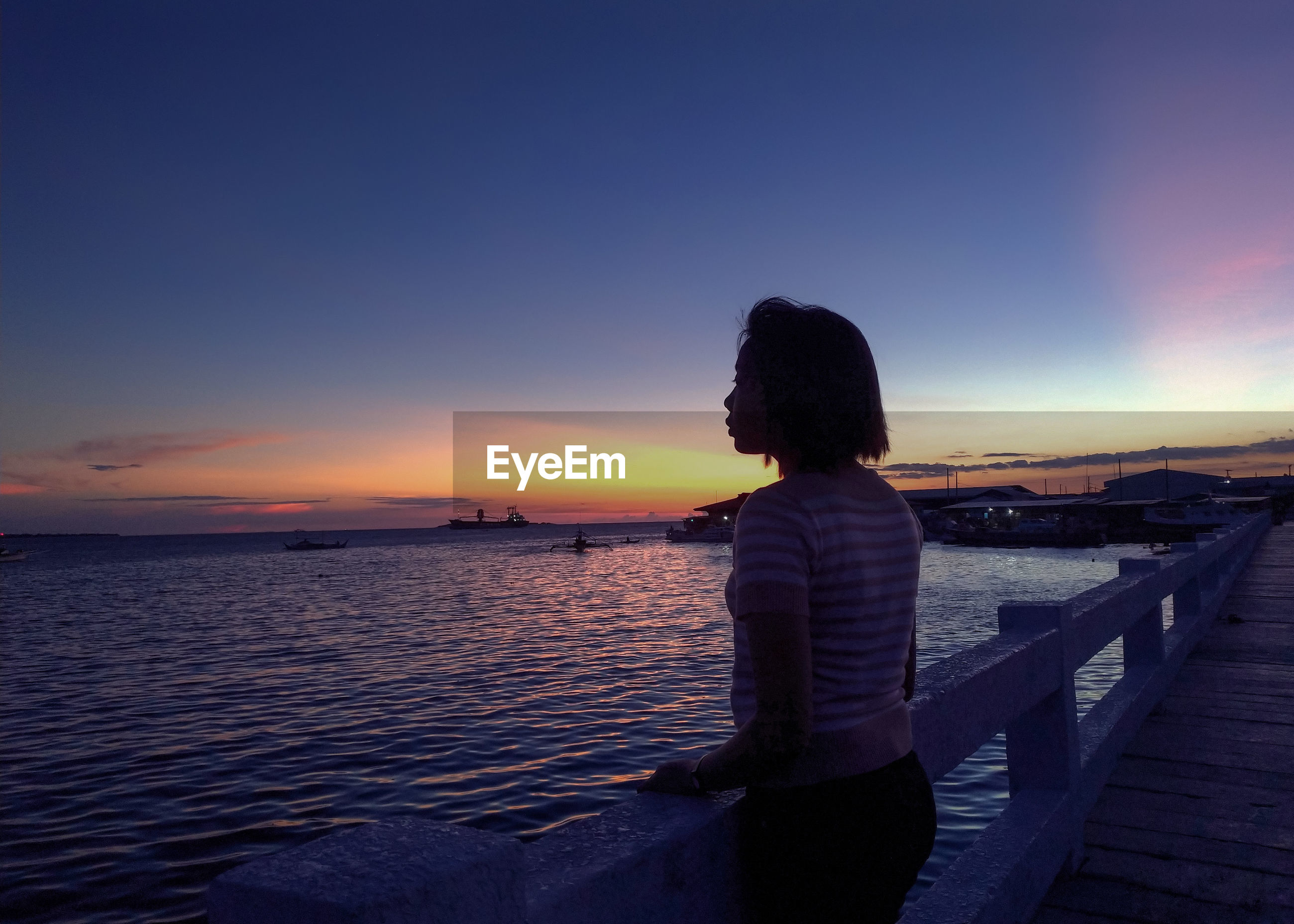 REAR VIEW OF WOMAN LOOKING AT SEA DURING SUNSET