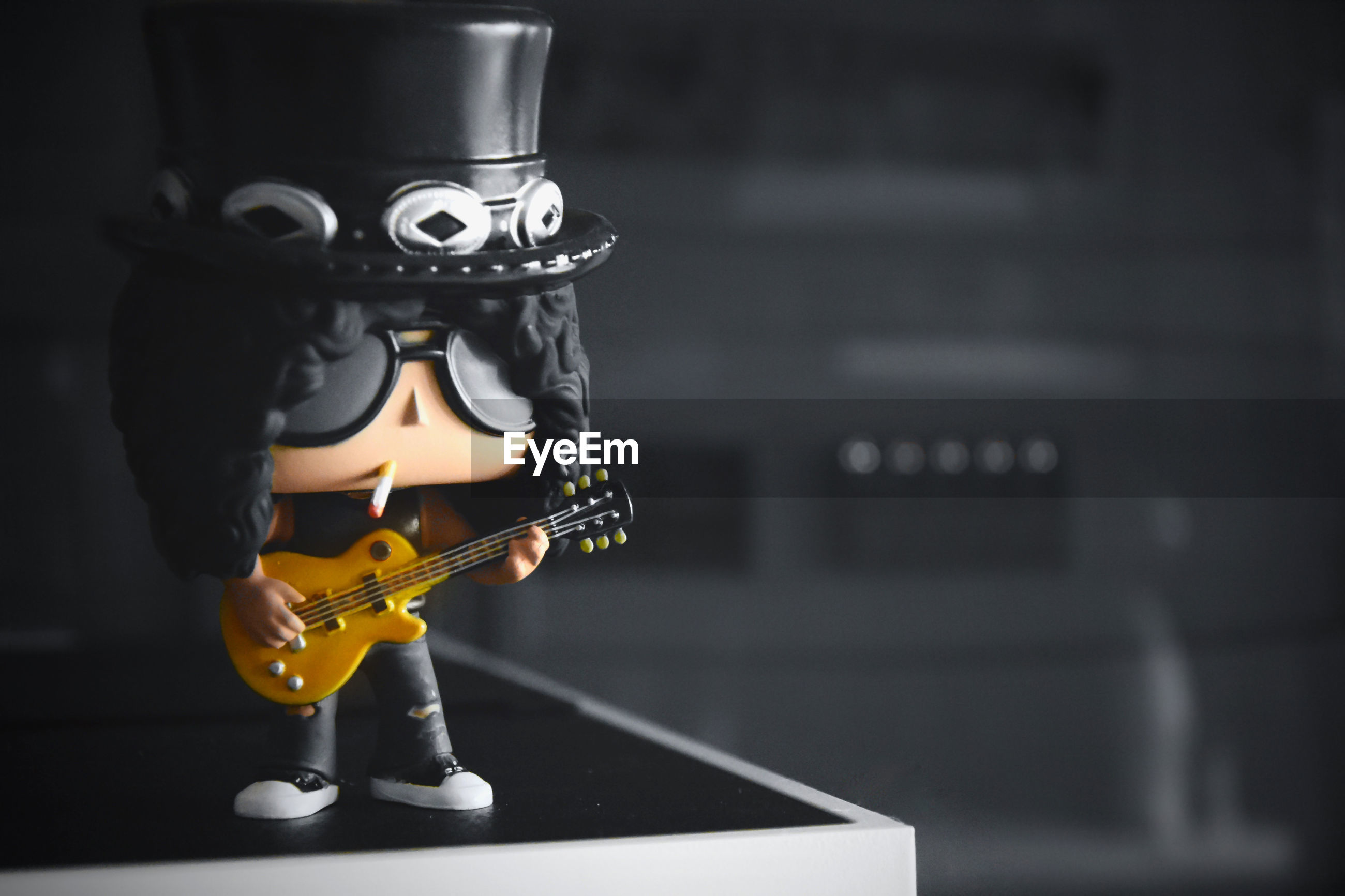 music, arts culture and entertainment, focus on foreground, musical instrument, string instrument, indoors, representation, creativity, guitar, art and craft, still life, metal, close-up, human representation, musical equipment, selective focus, playing, skill, no people, figurine