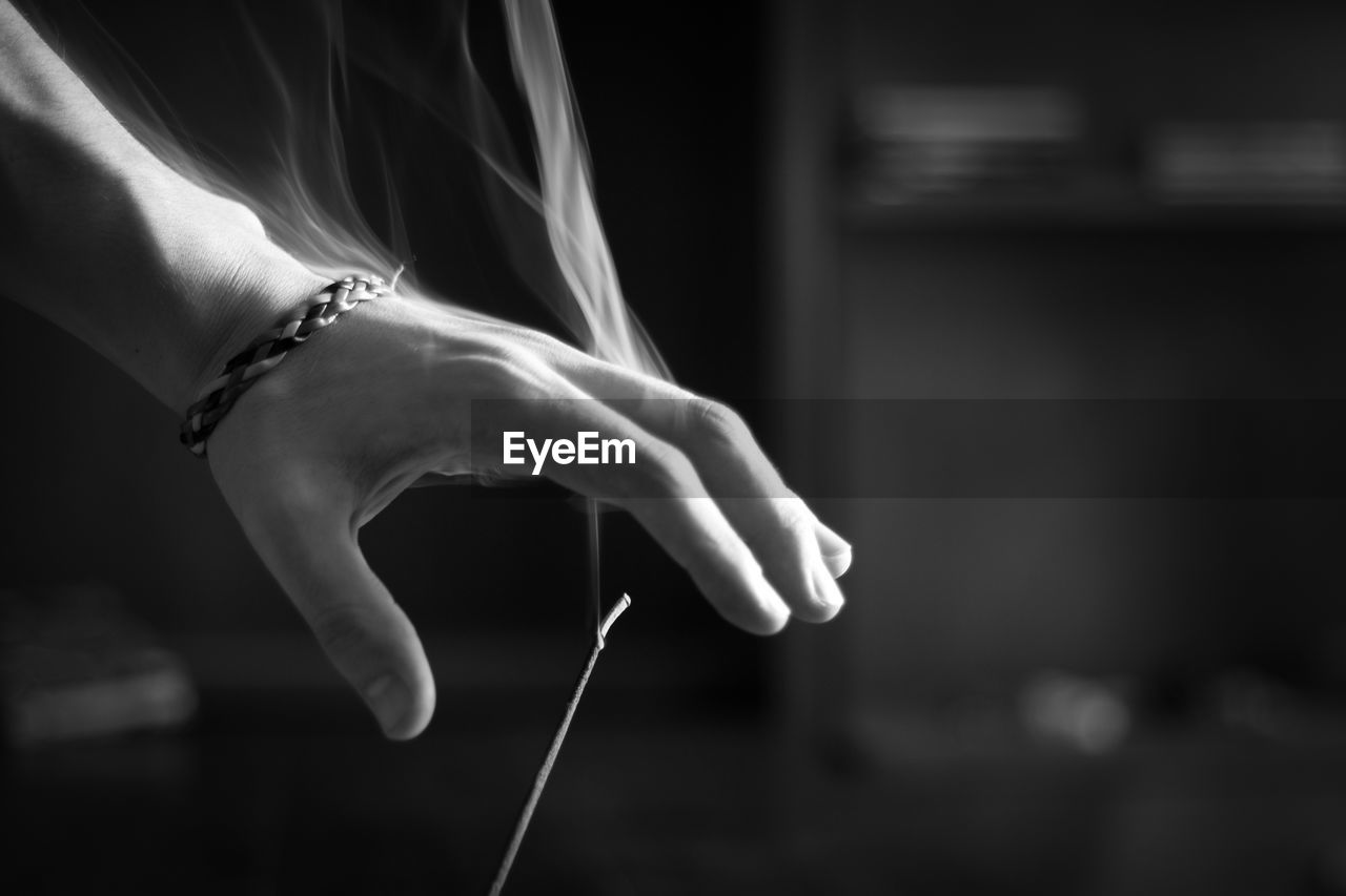 Cropped Hand Of Woman Over Burning Incense