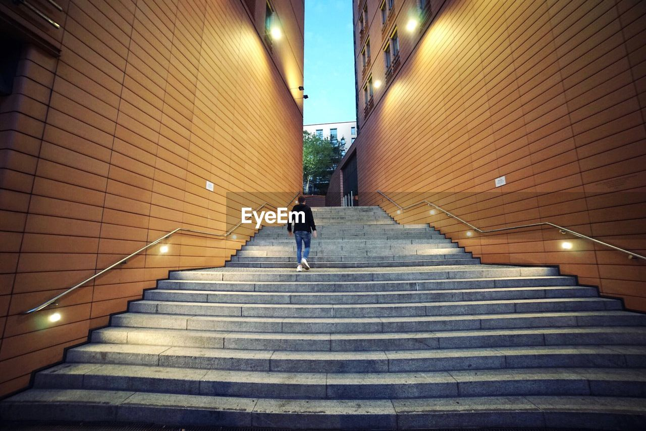 staircase, architecture, steps and staircases, built structure, illuminated, real people, direction, the way forward, one person, men, lifestyles, moving up, subway, indoors, railing, walking, wall - building feature, lighting equipment, low angle view, modern, underground walkway, underpass, ceiling