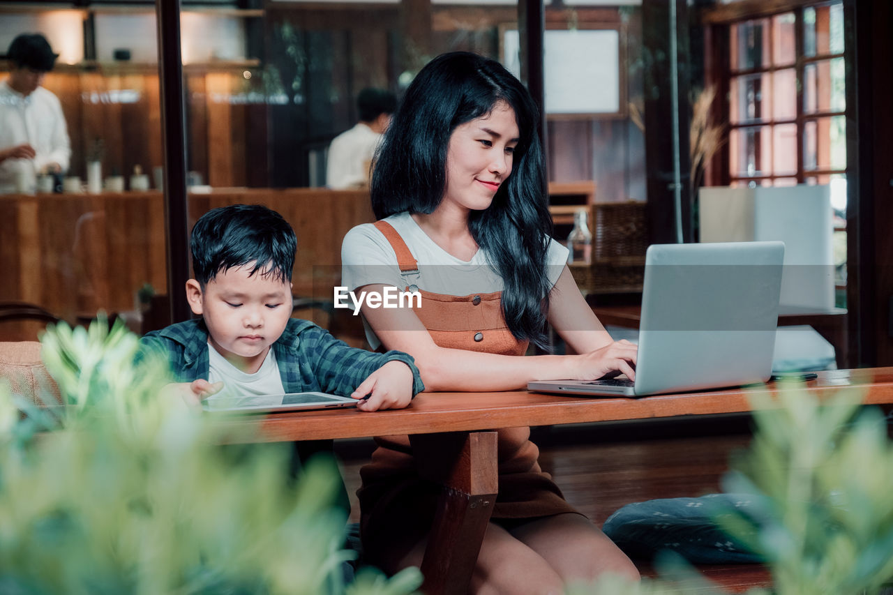 laptop, wireless technology, using laptop, women, family, technology, females, real people, computer, table, child, communication, togetherness, two people, adult, casual clothing, lifestyles, men, mother, childhood, daughter
