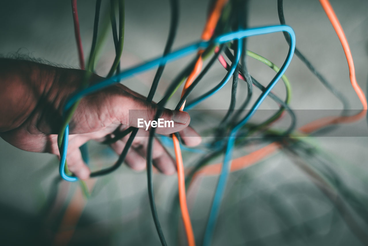 Cropped Hand Of Man Amidst Colorful Wires