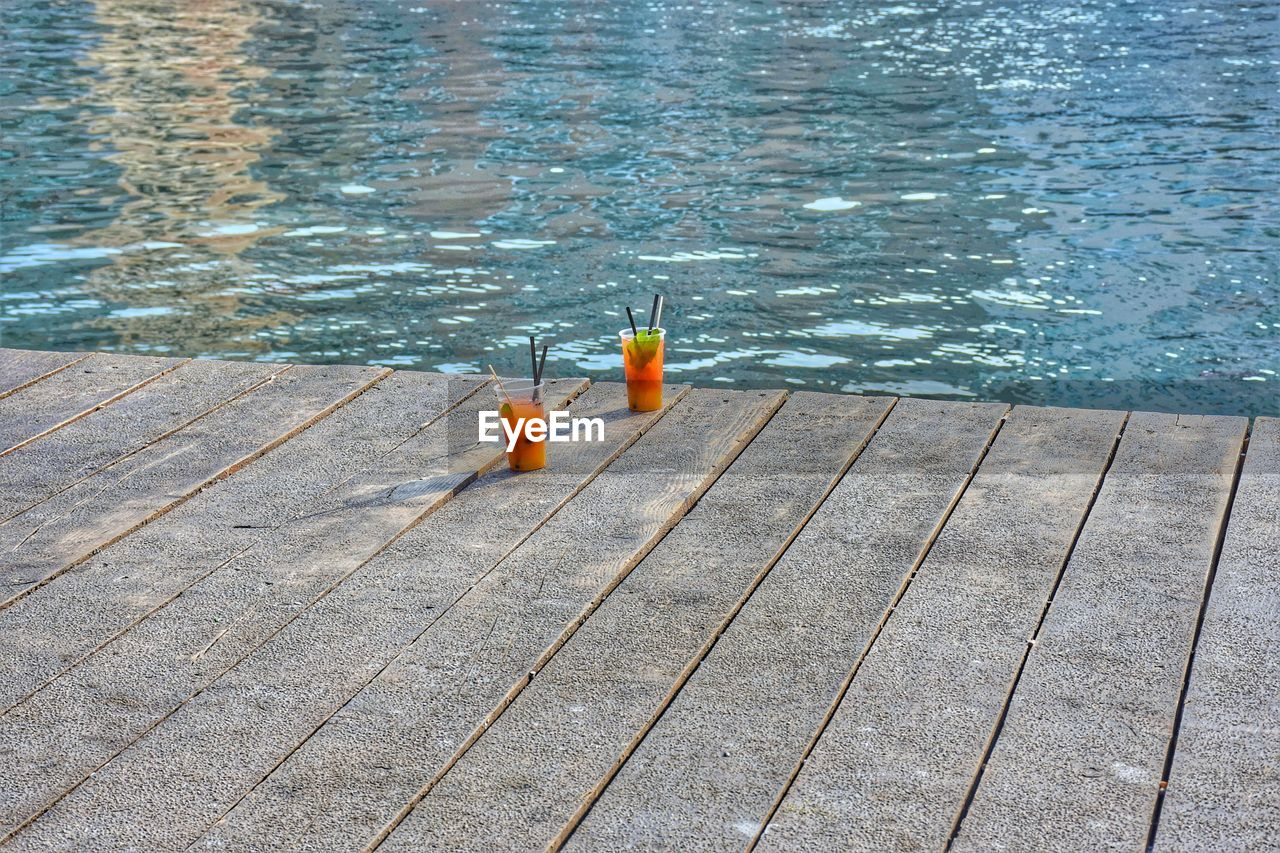 water, no people, nature, day, safety, wood - material, outdoors, rippled, security, orange color, swimming pool, high angle view, bottle, protection, reflection, pool, pier, food and drink, tranquility, floating on water