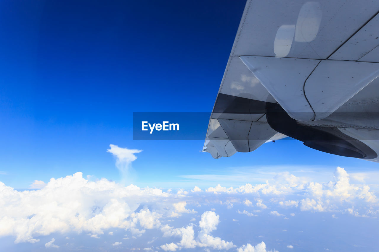 sky, cloud - sky, blue, nature, no people, low angle view, day, mode of transportation, transportation, flying, air vehicle, outdoors, sunlight, mid-air, motion, airplane, white color, on the move, aircraft wing, environment
