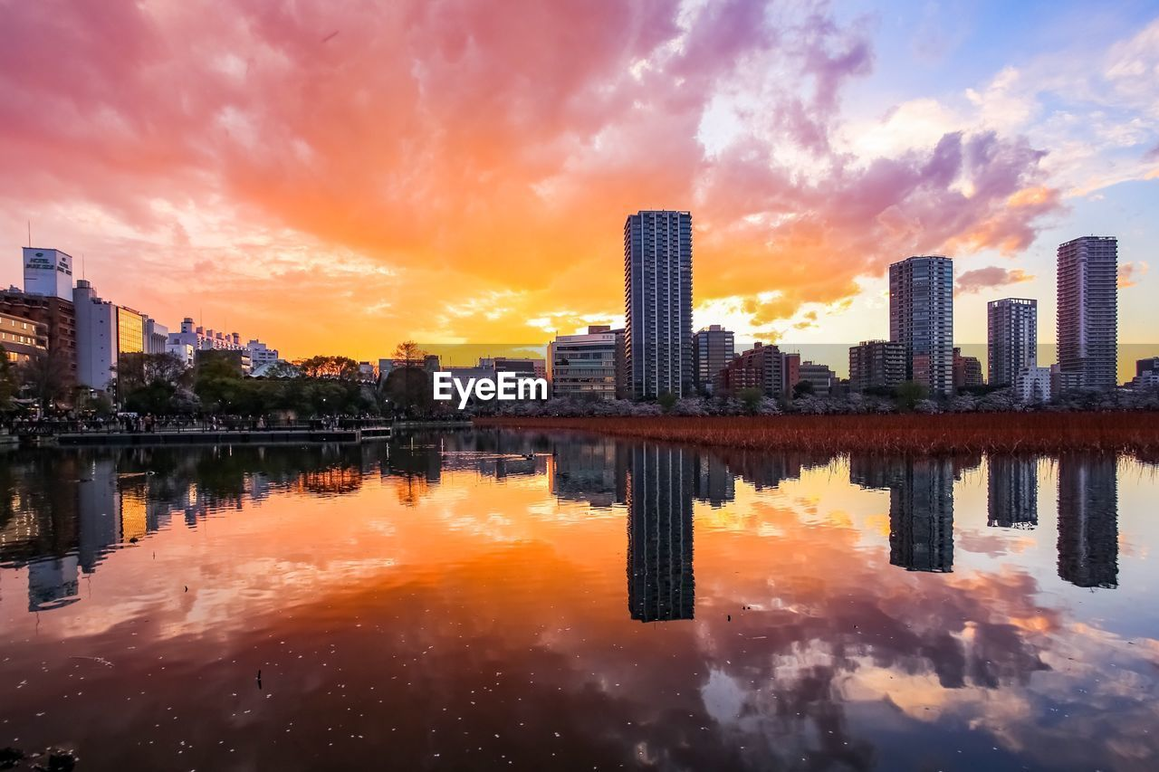 building exterior, architecture, sky, built structure, cloud - sky, sunset, city, reflection, orange color, building, water, nature, office building exterior, waterfront, cityscape, no people, urban skyline, skyscraper, outdoors, financial district