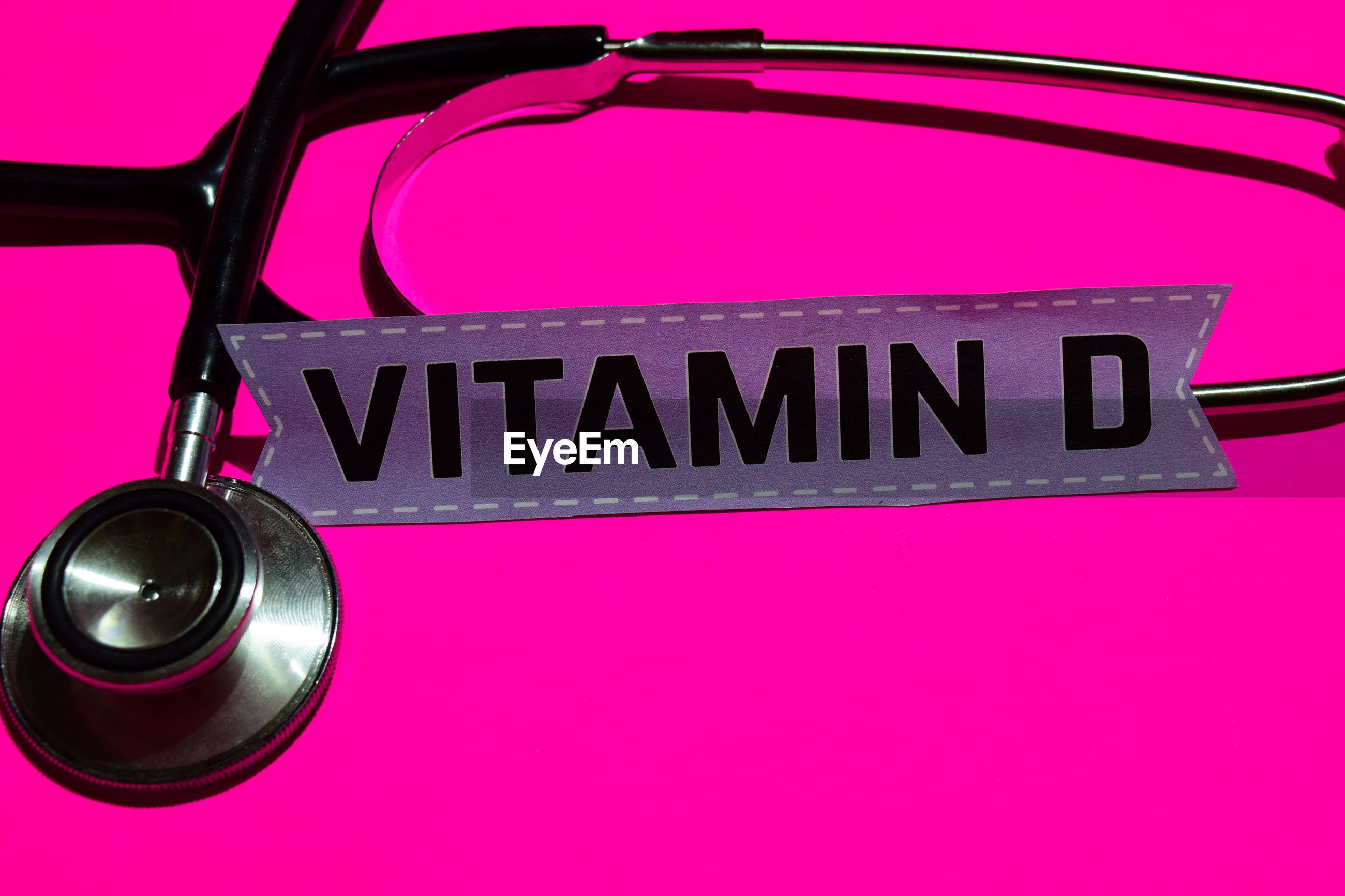 High angle view of stethoscope by text on pink background