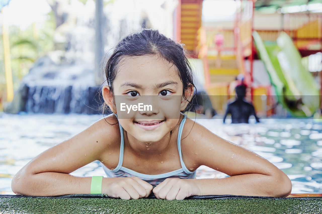 one person, portrait, child, looking at camera, childhood, real people, front view, leisure activity, lifestyles, innocence, day, smiling, focus on foreground, lying on front, emotion, girls, cute, outdoors, swimming pool