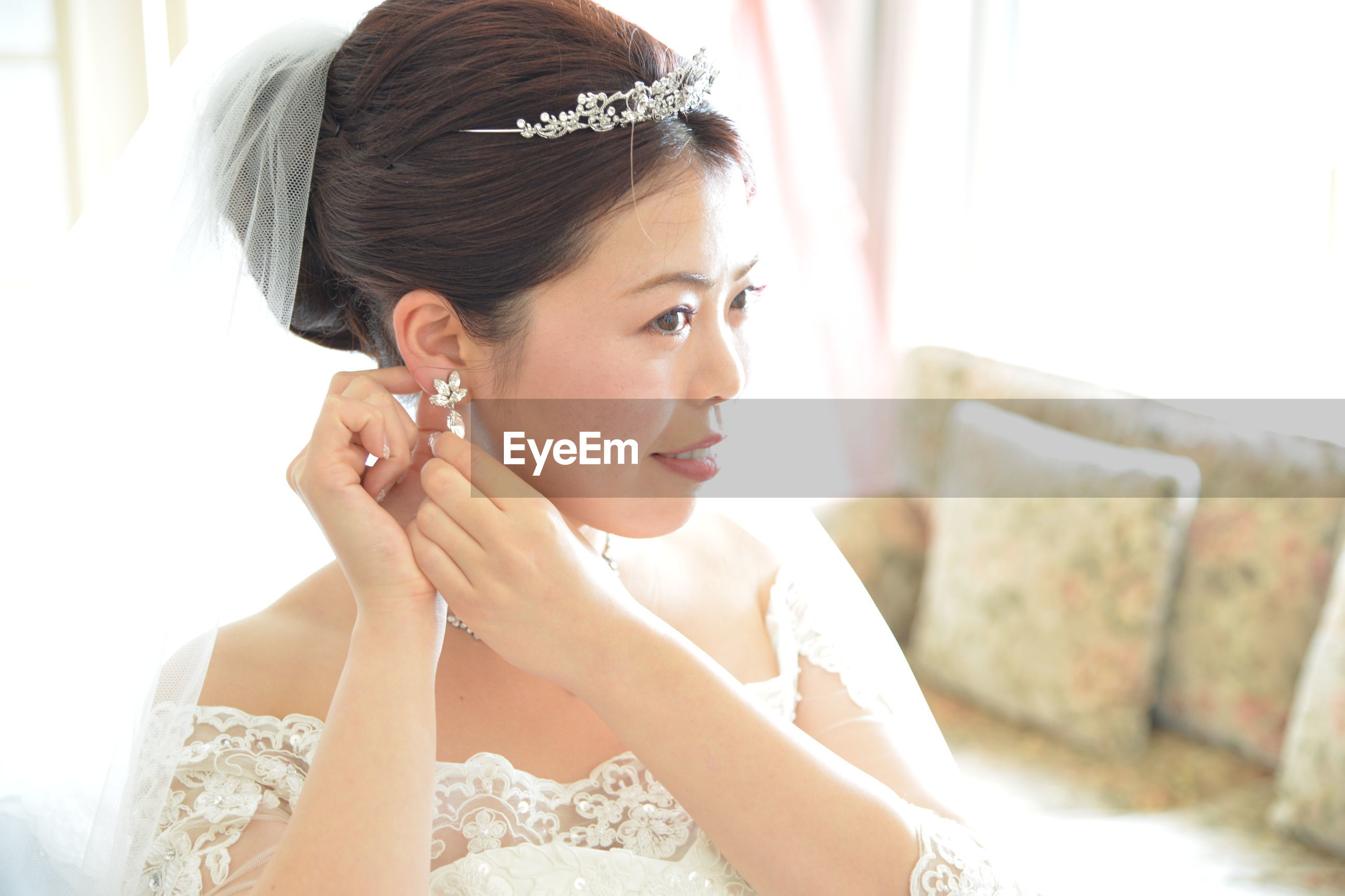 Close-up of bride wearing earring at home