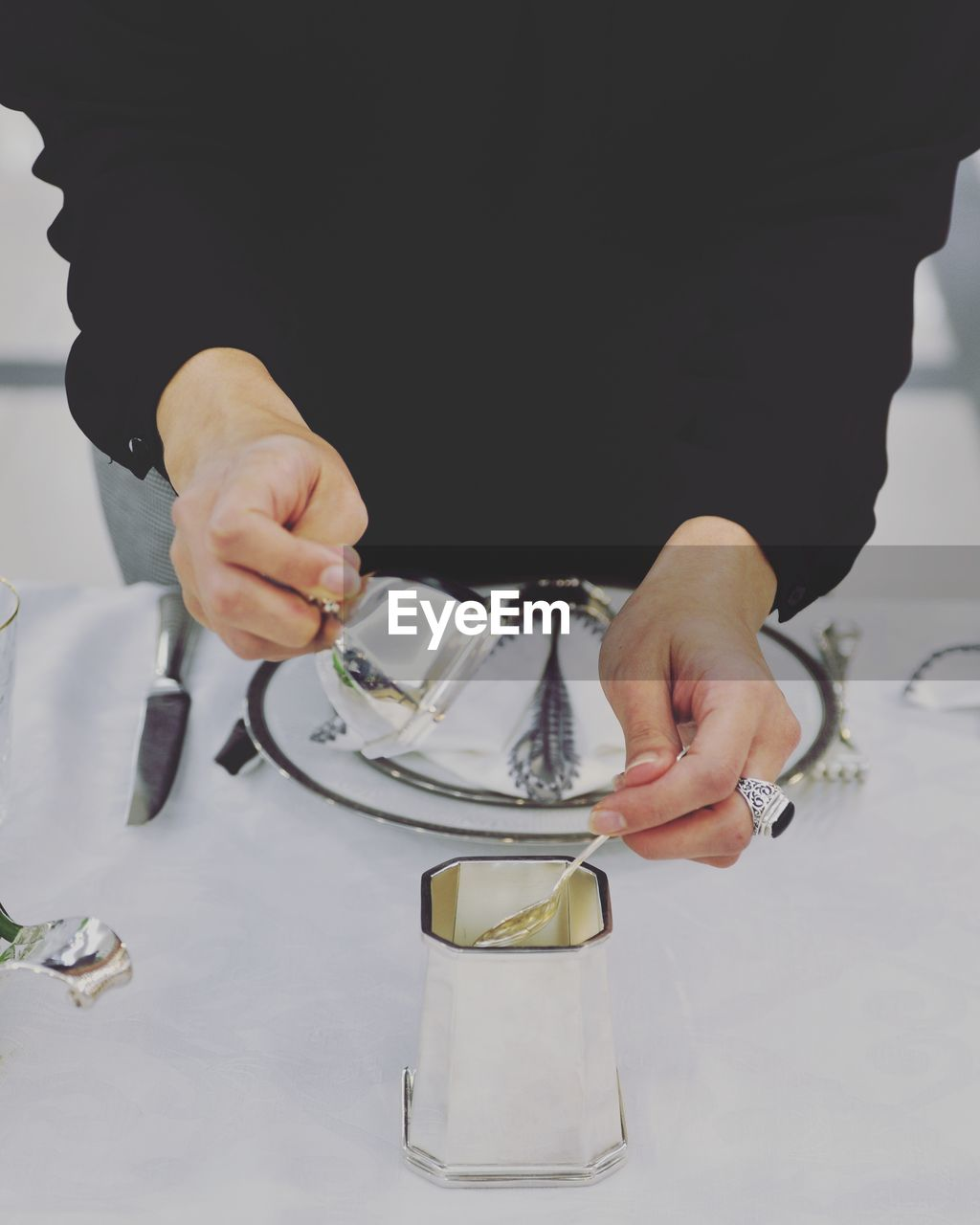 Midsection of person holding spoon in container on table