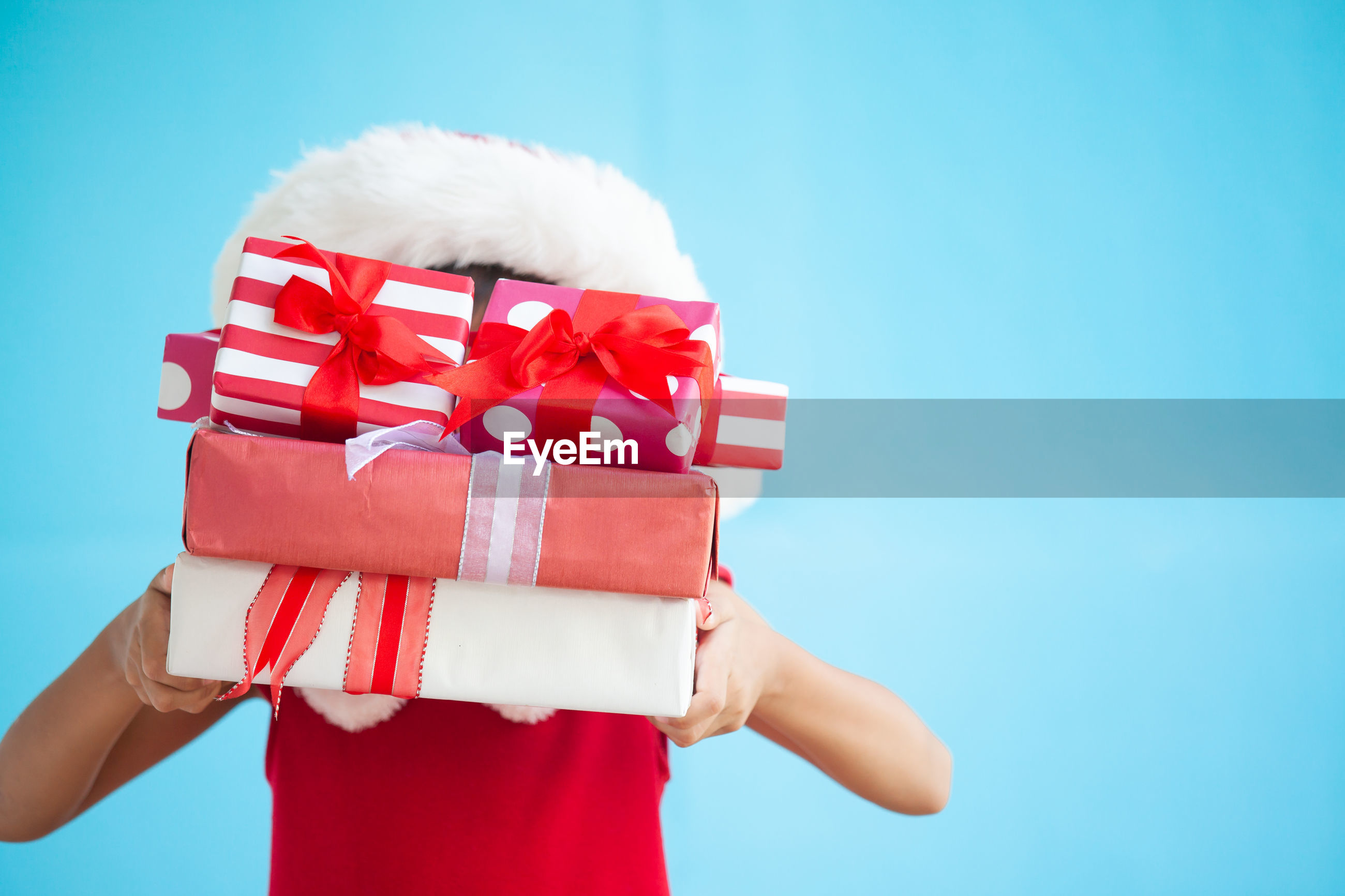 Girl covering face with gift boxes against blue background