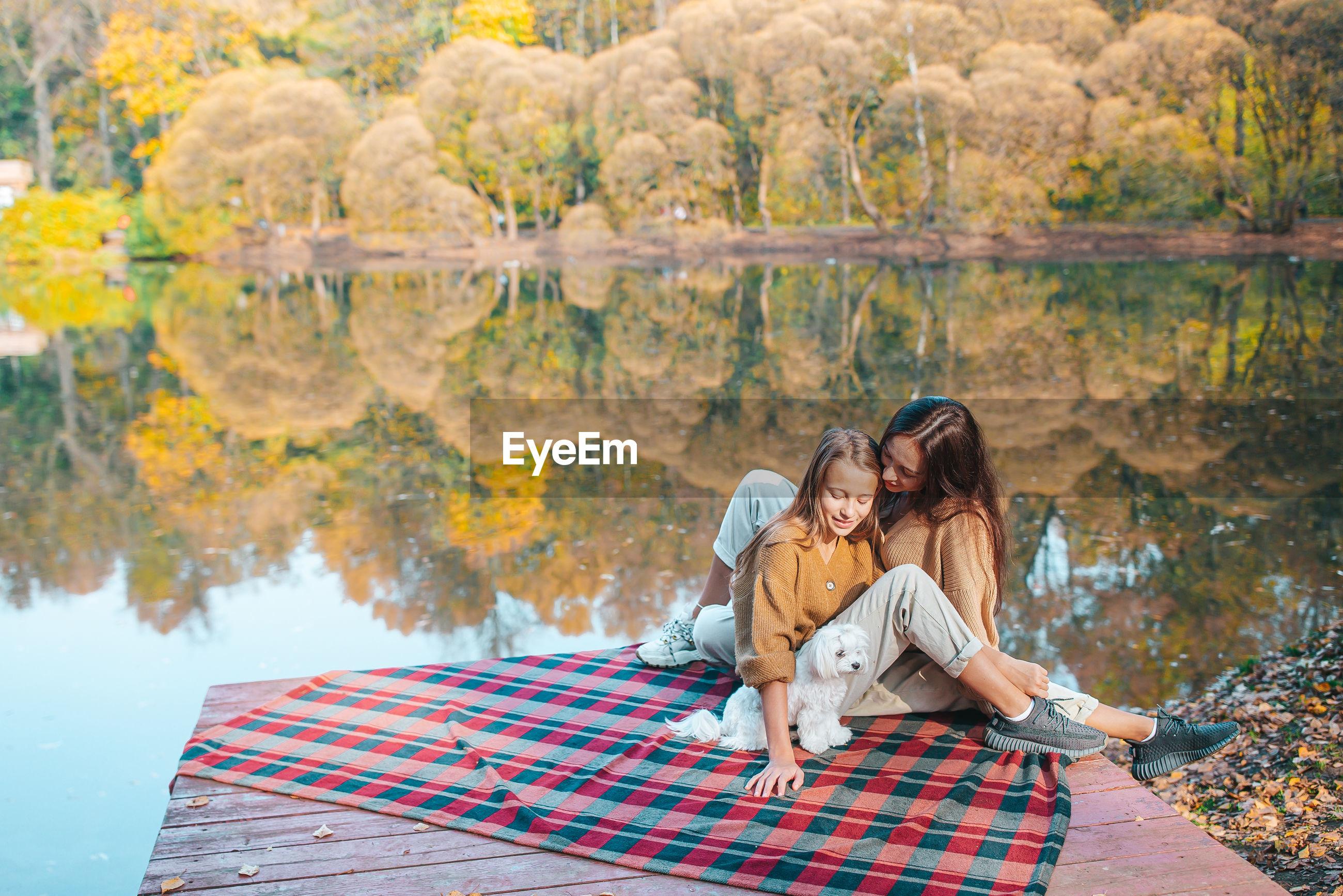 Family sitting by lake
