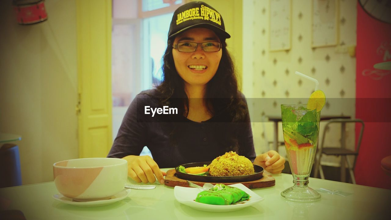 table, food and drink, food, restaurant, indoors, plate, fork, front view, sitting, one person, real people, eyeglasses, freshness, close-up, day, people
