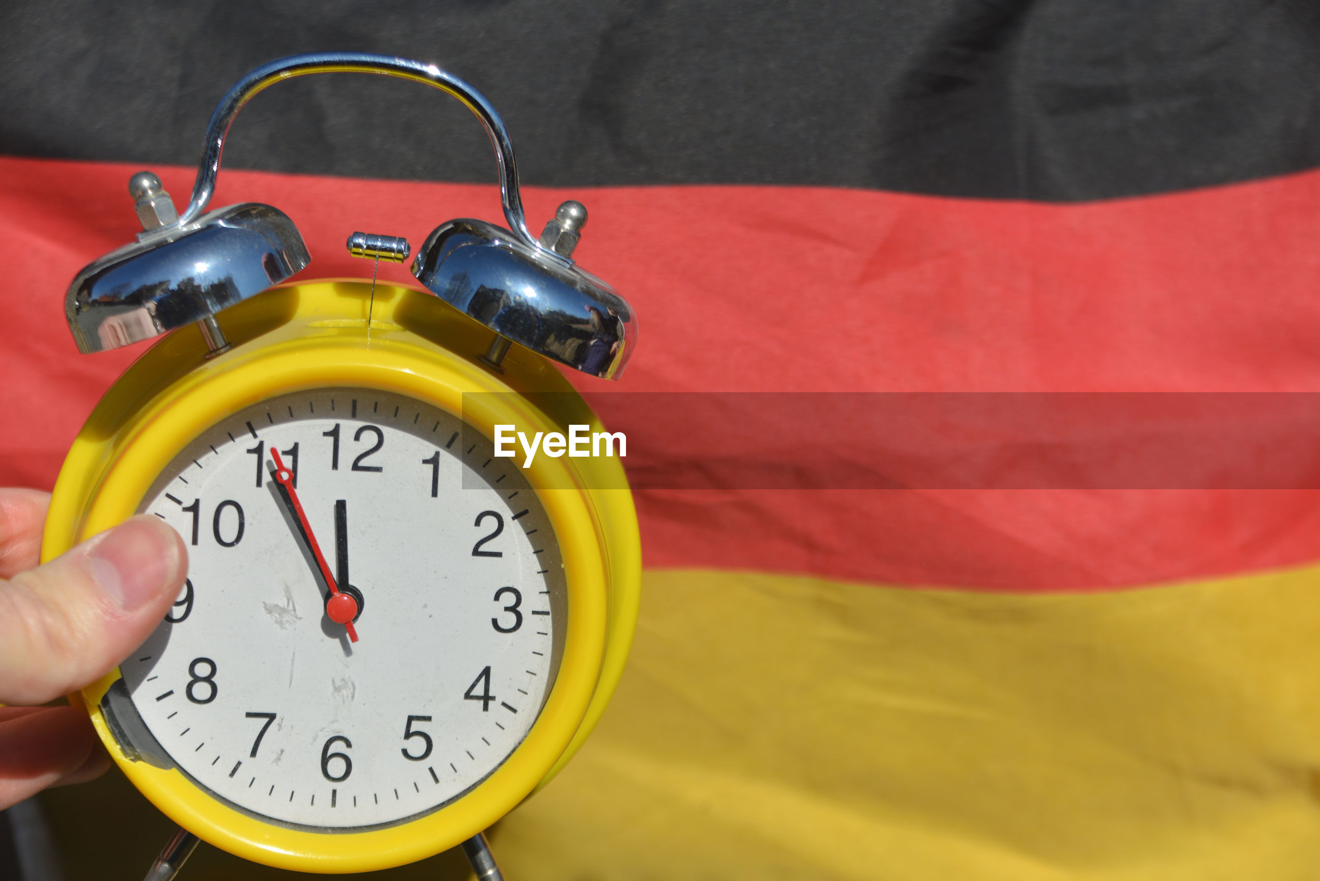 Close-up of hand holding alarm clock against german flag