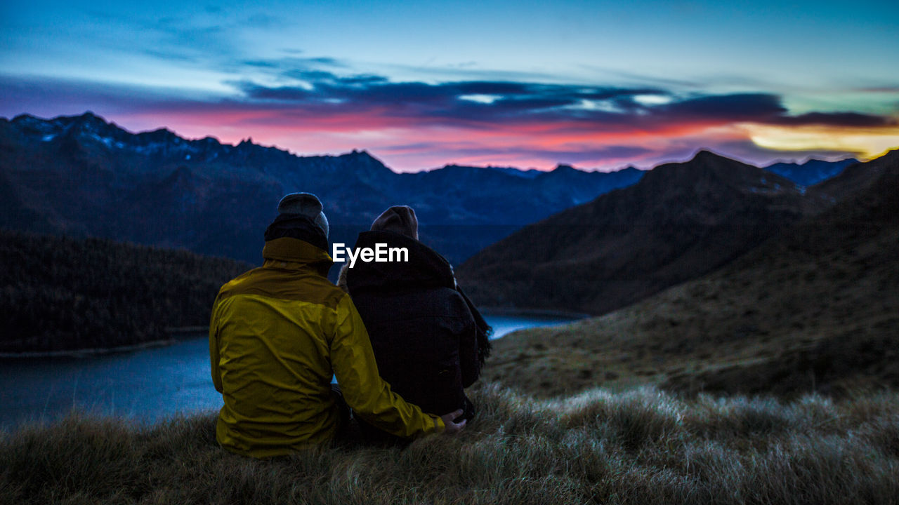 Rear View Of Couple Sitting On Grassy Field Against Lake During Sunset