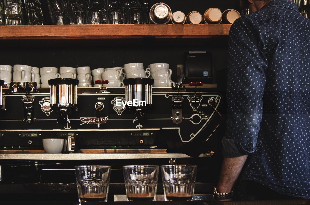 drink, refreshment, food and drink, bar - drink establishment, real people, alcohol, indoors, one person, coffee - drink, bar counter, coffee, business, container, midsection, standing, glass, food and drink industry, cup, mug, bartender, coffee shop, nightlife