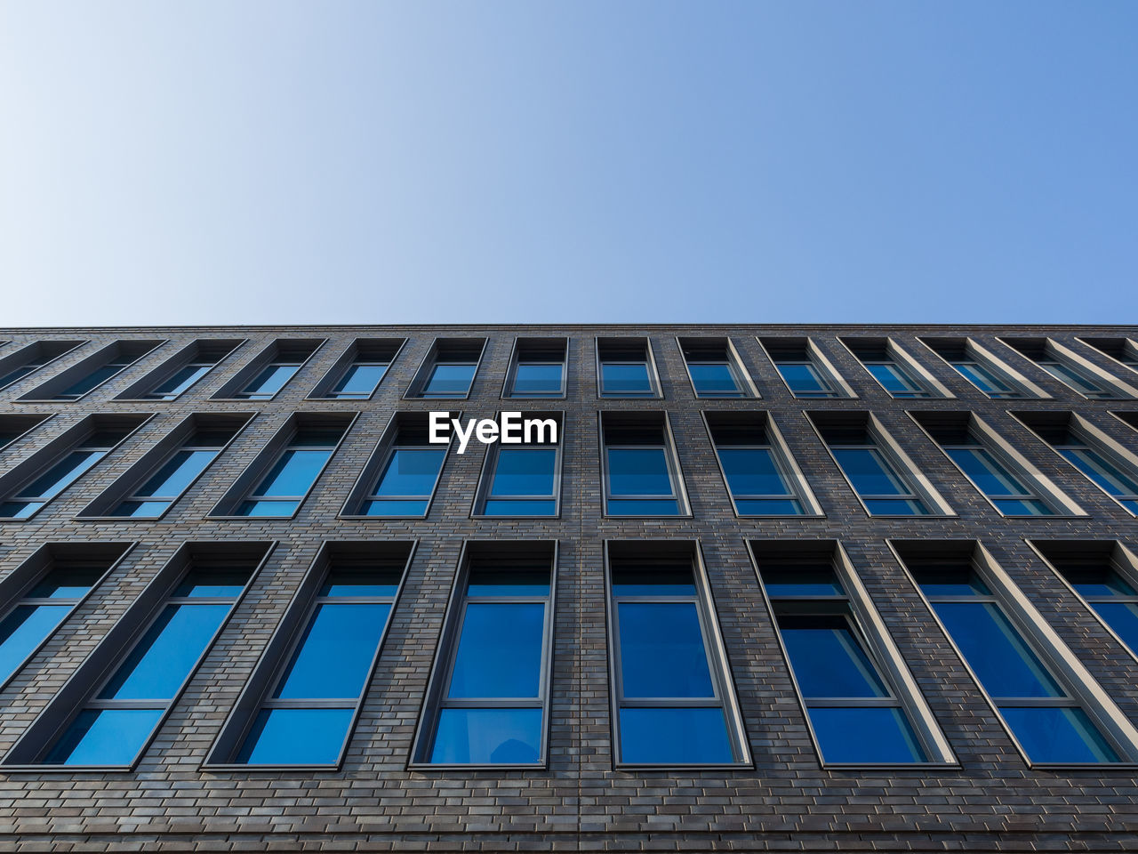 Low Angle View Of Facade Of Building Against Blue Sky