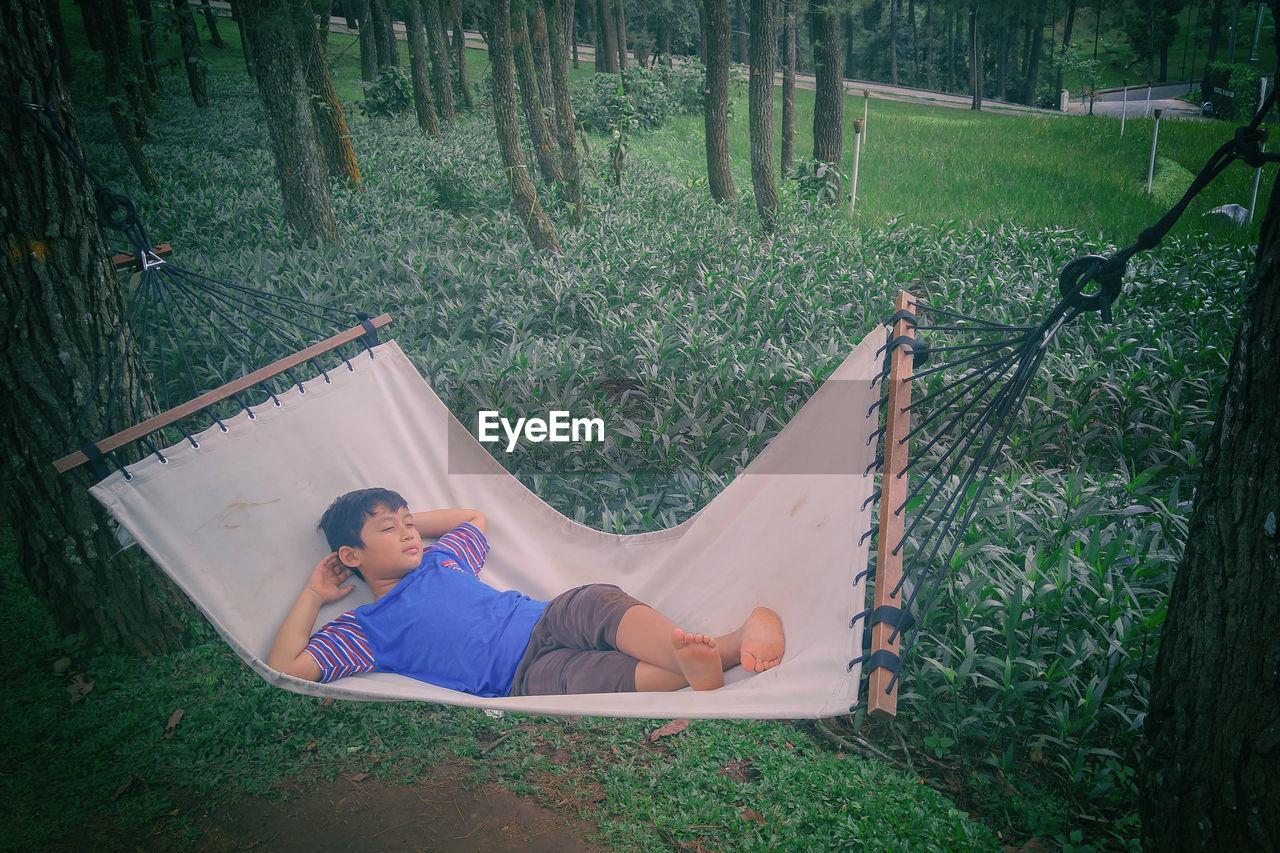 View Of Boy Relaxing In Hammock