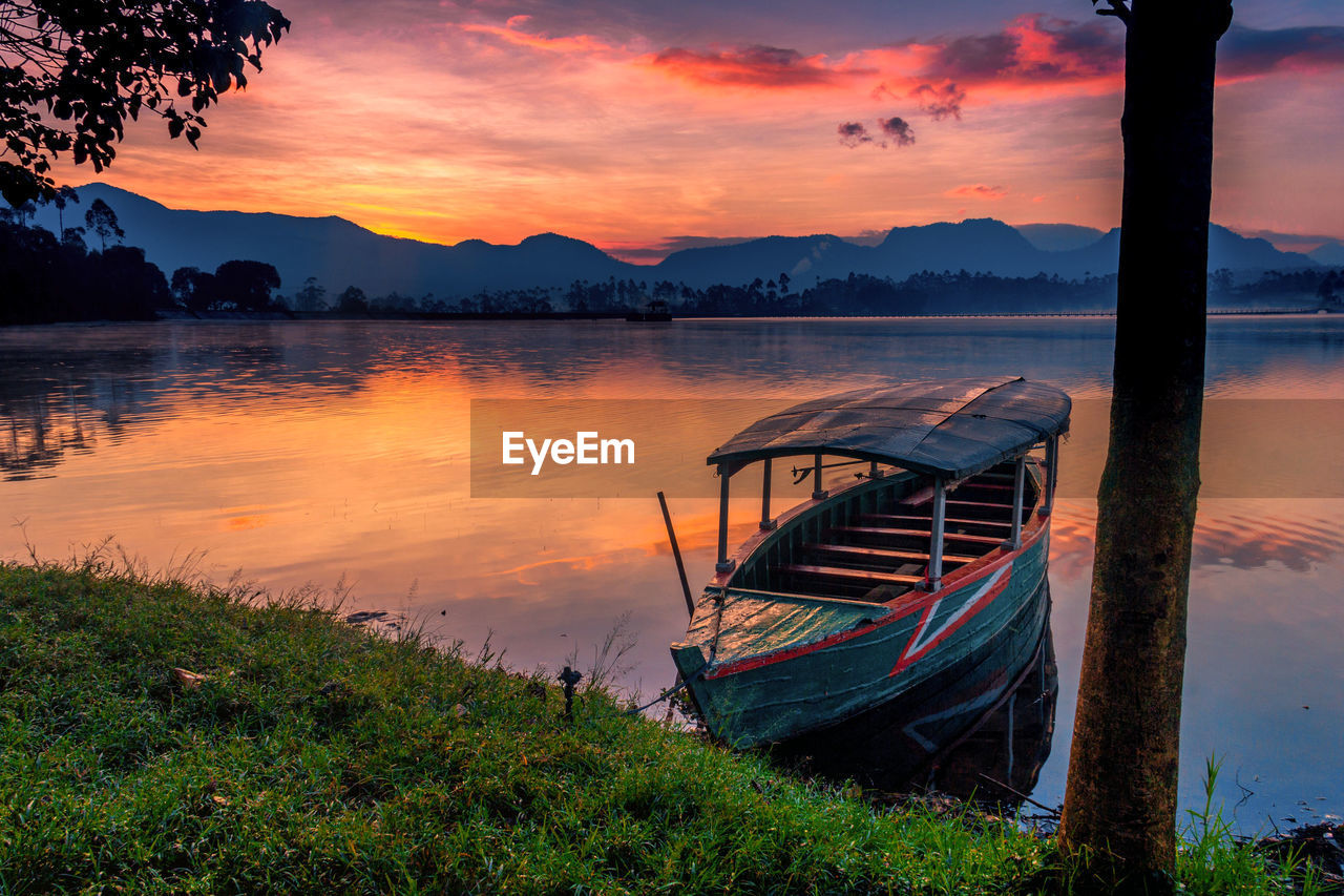 sky, sunset, water, scenics - nature, beauty in nature, nautical vessel, tranquility, cloud - sky, nature, tranquil scene, mode of transportation, orange color, lake, moored, mountain, transportation, no people, plant, idyllic, mountain range, outdoors