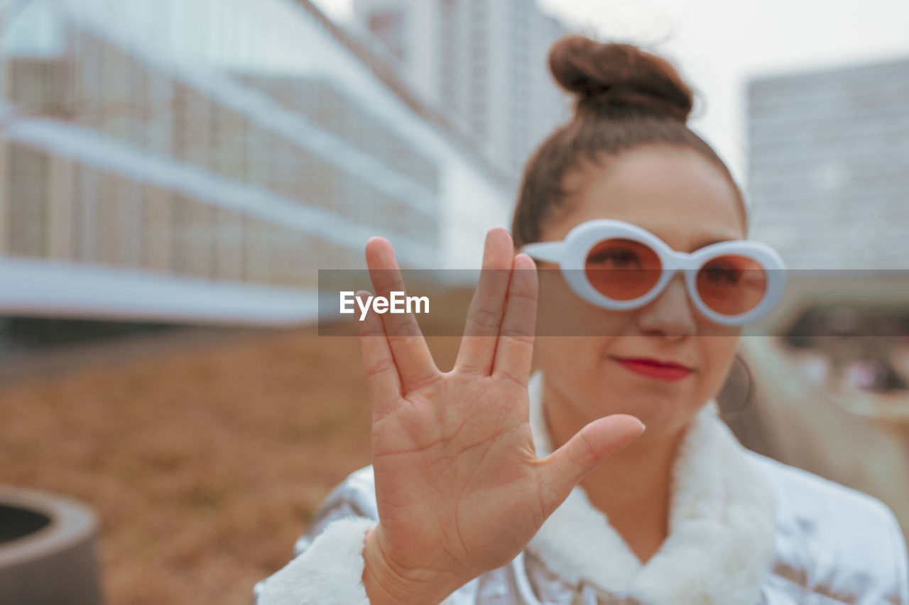 real people, women, focus on foreground, one person, portrait, lifestyles, human hand, headshot, sunglasses, hand, glasses, adult, fashion, leisure activity, gesturing, females, day, human body part, front view, finger, hairstyle