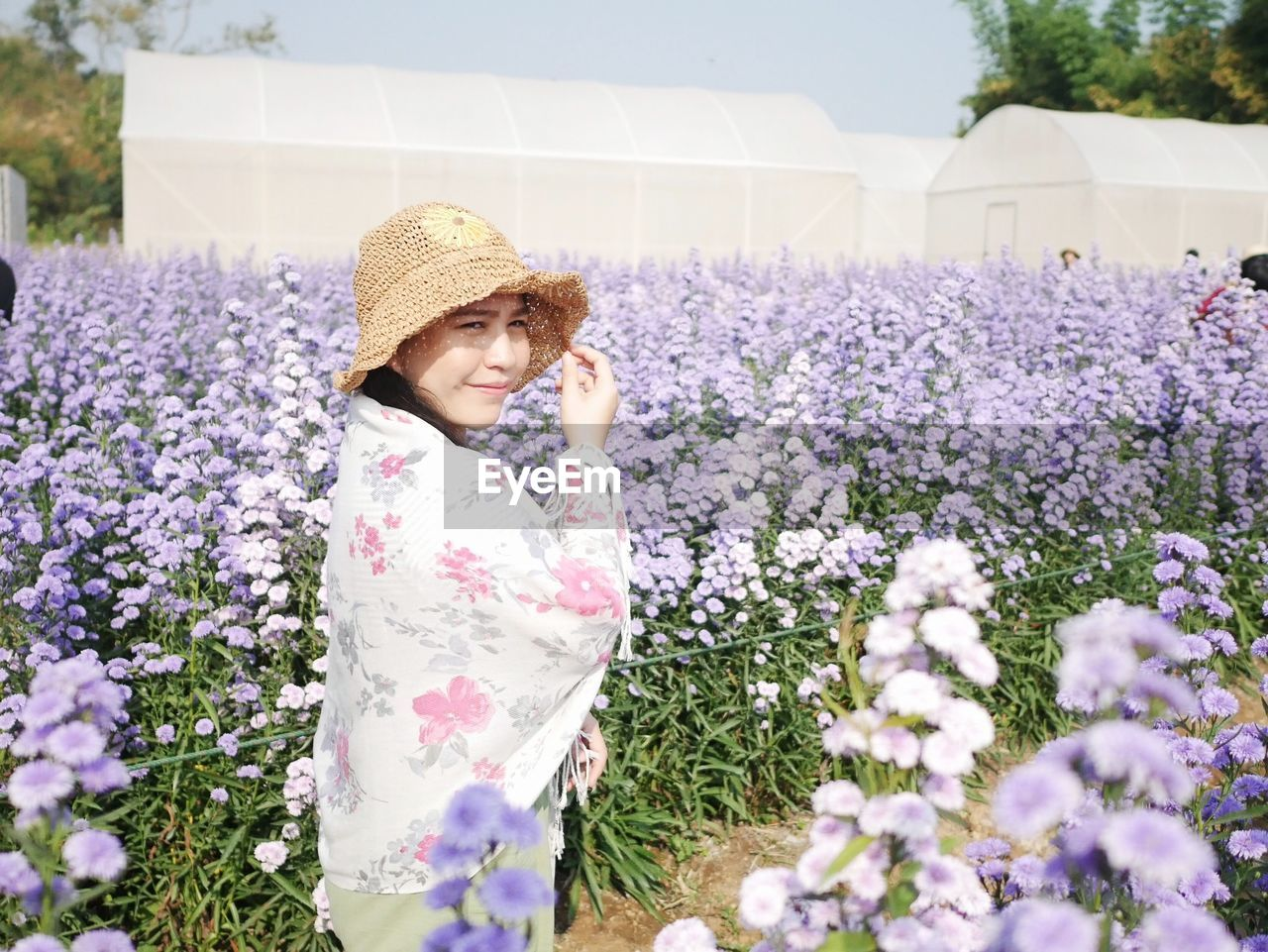 Young woman standing amidst flower field