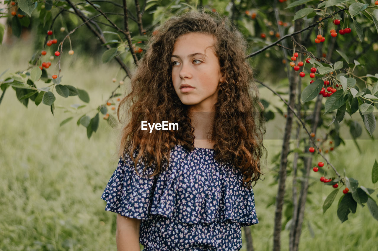 Portrait of teenage girl standing against plants