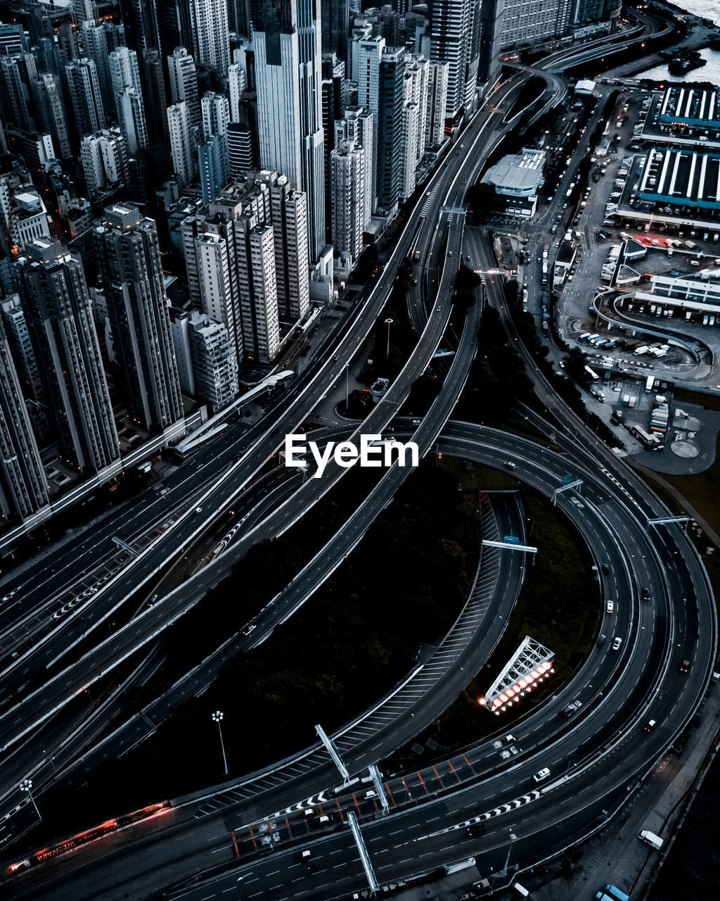city, architecture, transportation, building exterior, built structure, cityscape, office building exterior, mode of transportation, highway, connection, road, motion, no people, high angle view, skyscraper, building, elevated road, city life, street, aerial view, modern, multiple lane highway, complexity, outdoors, financial district