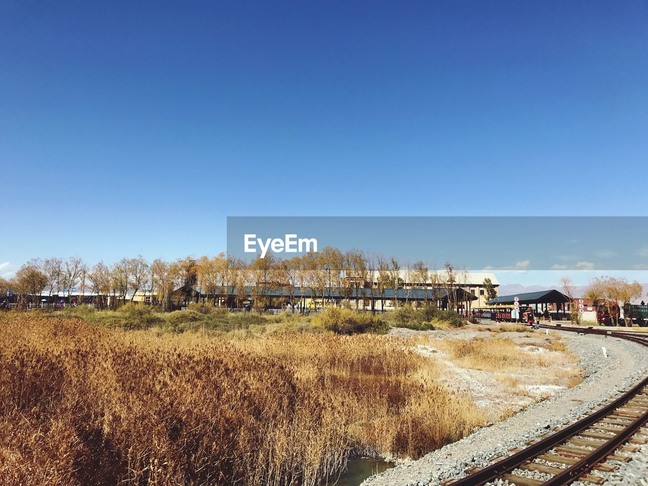 VIEW OF RAILROAD TRACK AGAINST CLEAR BLUE SKY