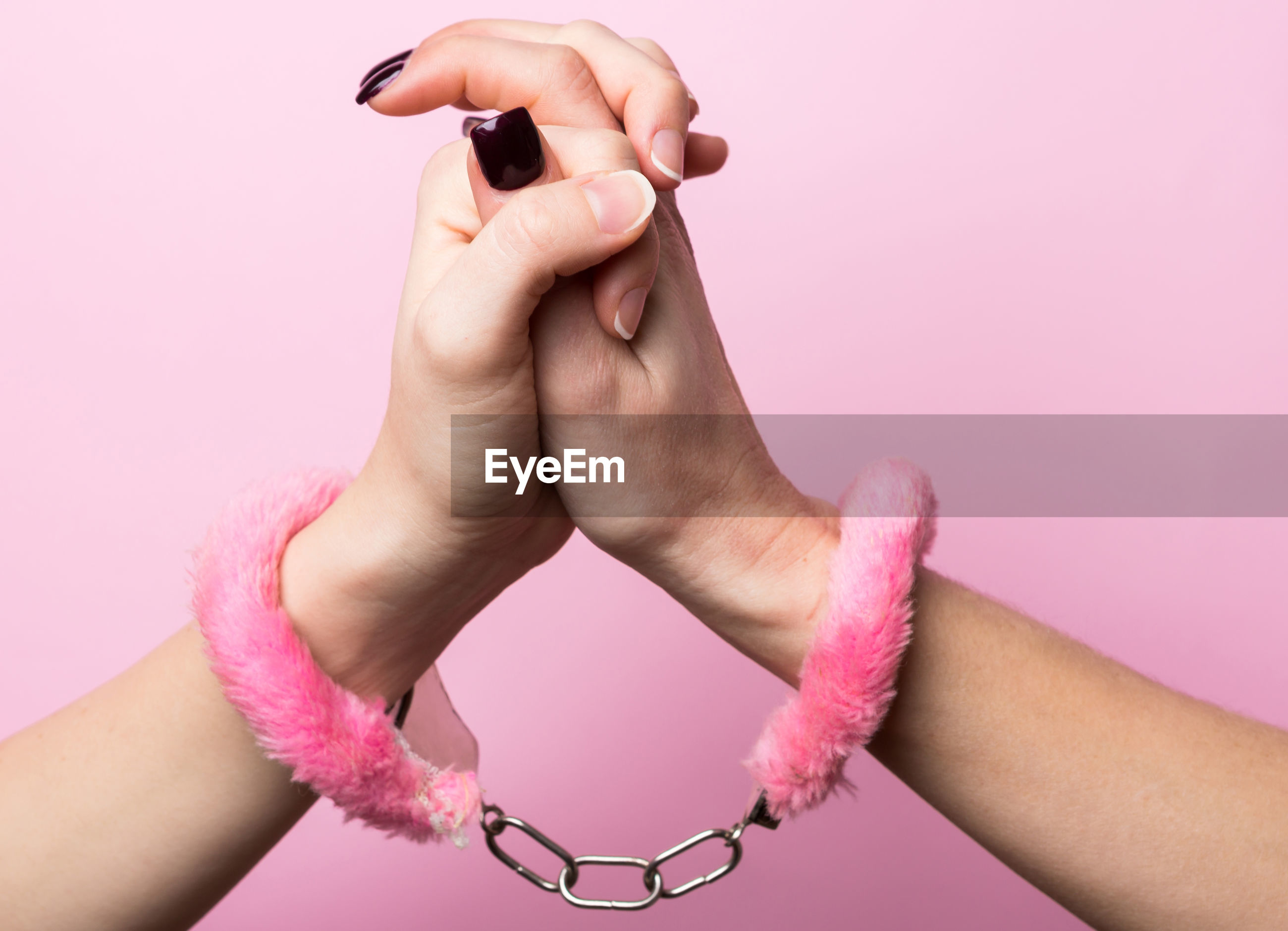 Cropped hands of woman wearing handcuffs against wall