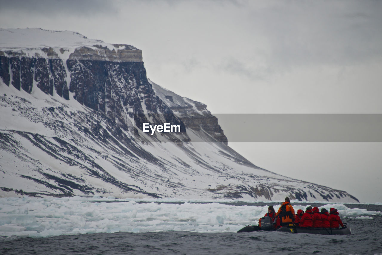 People Rafting In River By Snowcapped Mountain Against Sky