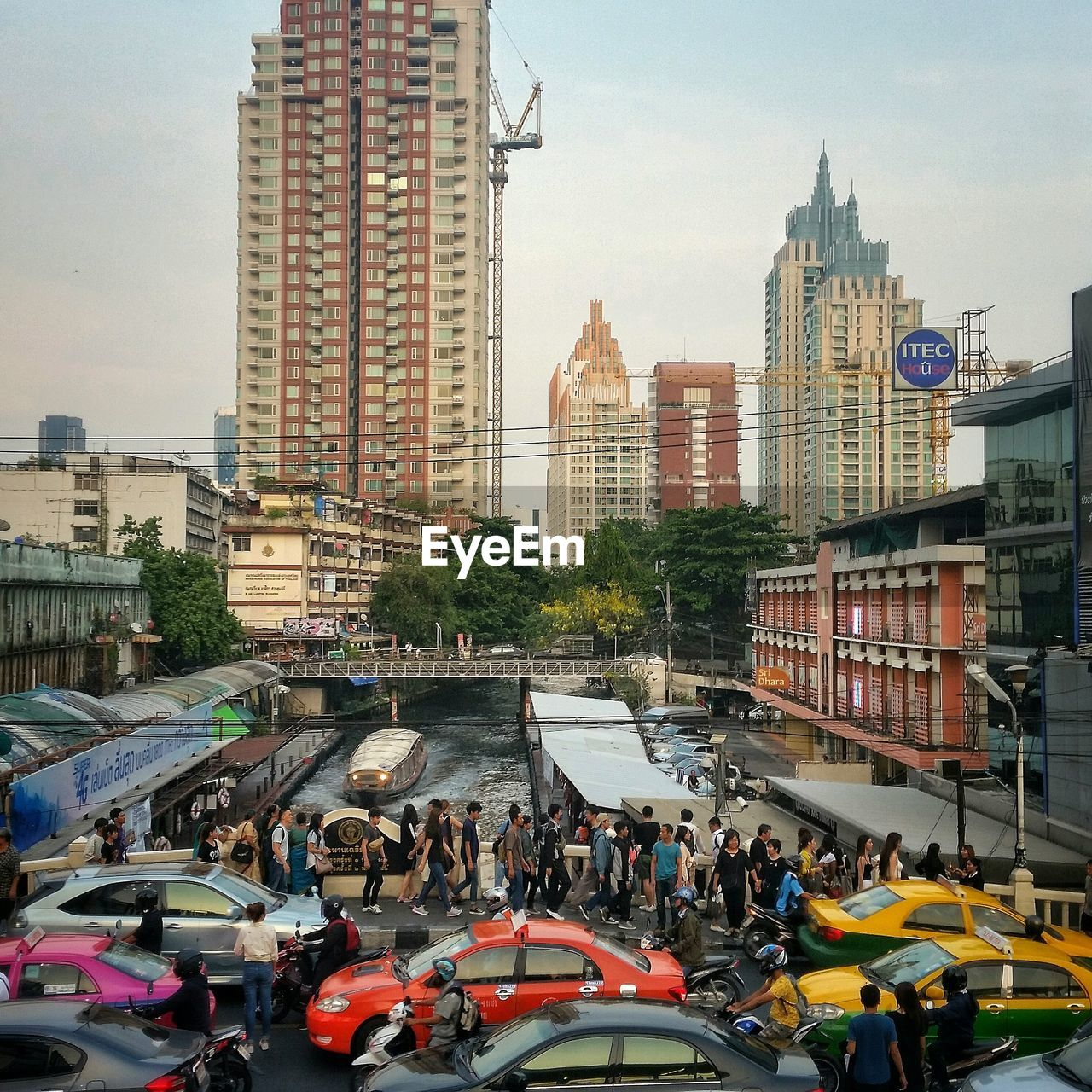 architecture, building exterior, built structure, city, transportation, large group of people, land vehicle, real people, city life, mode of transport, car, skyscraper, day, outdoors, men, cityscape, sky, women, modern, crowd, people
