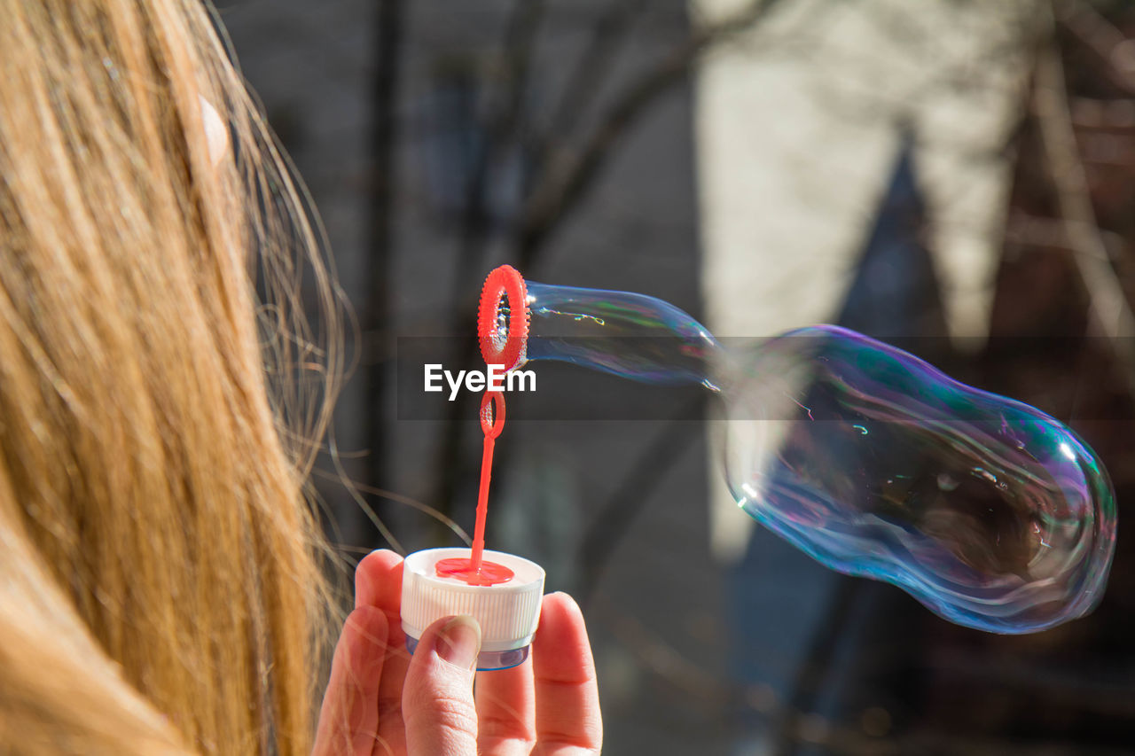 View of woman holding bubble wand