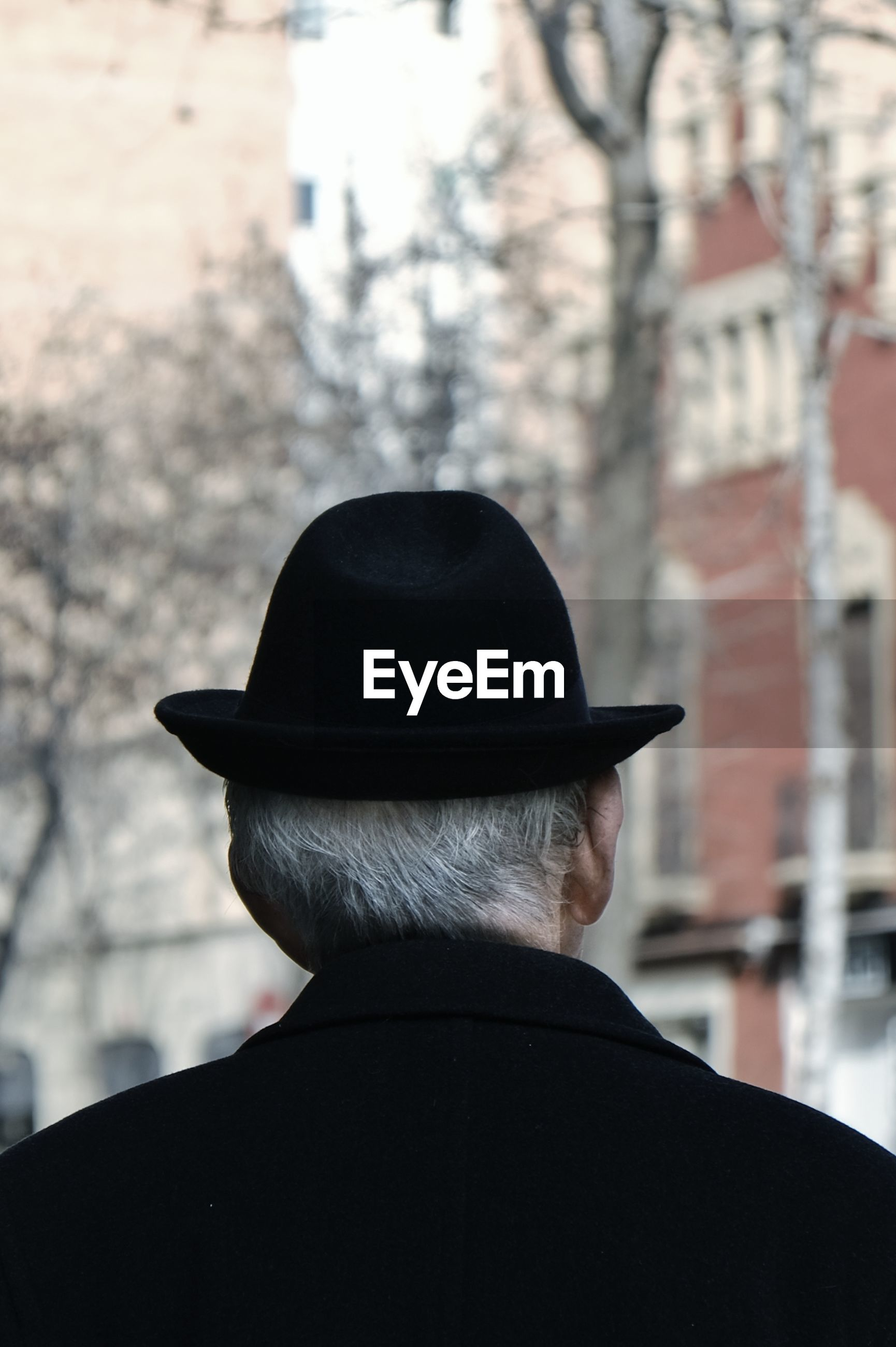 REAR VIEW OF MAN WEARING HAT AGAINST CITY
