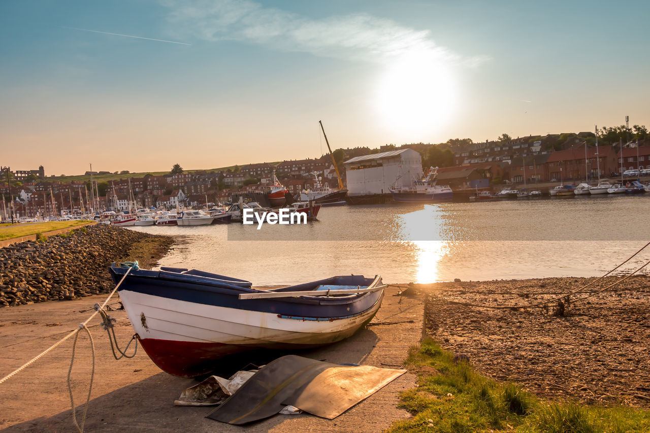 nautical vessel, water, transportation, mode of transportation, sky, moored, nature, no people, sunset, sunlight, architecture, building exterior, built structure, beach, land, reflection, river, city, outdoors, rowboat
