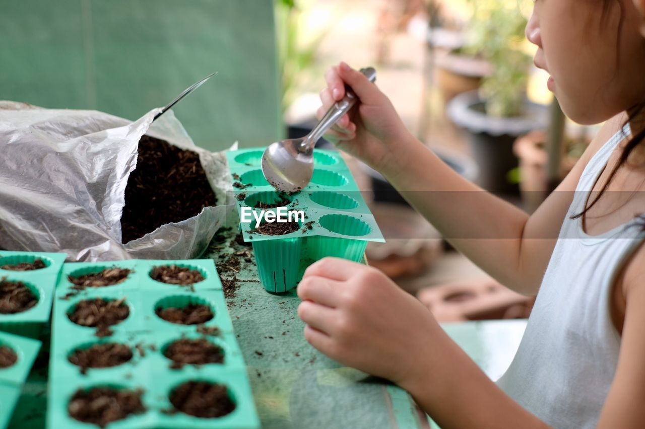 Midsection of girl putting dirt into silicone tray