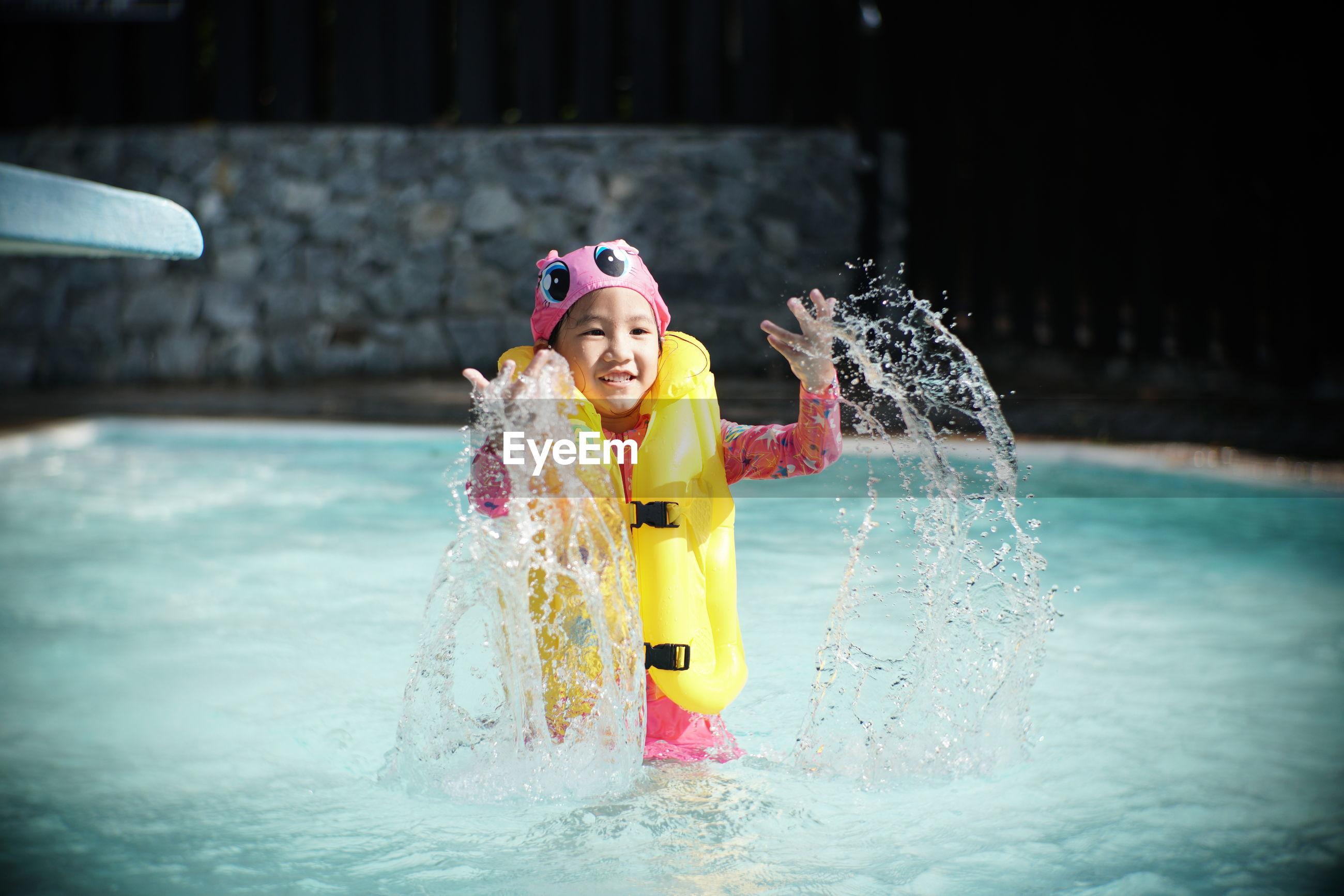 Smiling girl splashing water in swimming pool