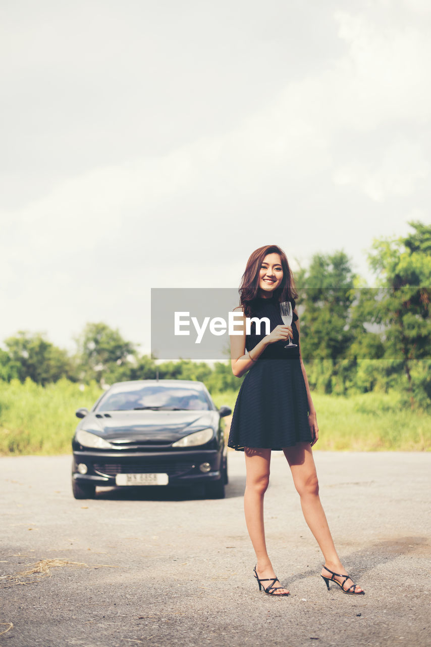 Portrait Of Smiling Young Woman With Drink Standing Against Car On Road