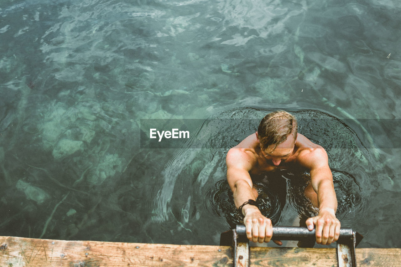 High angle view of shirtless man in lake