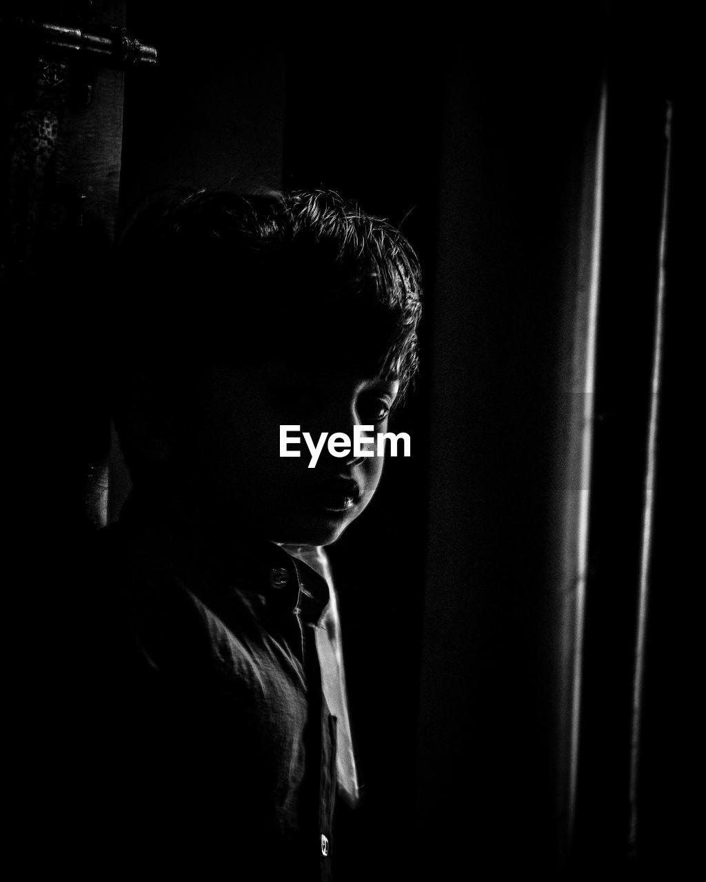 Portrait of boy standing in darkroom
