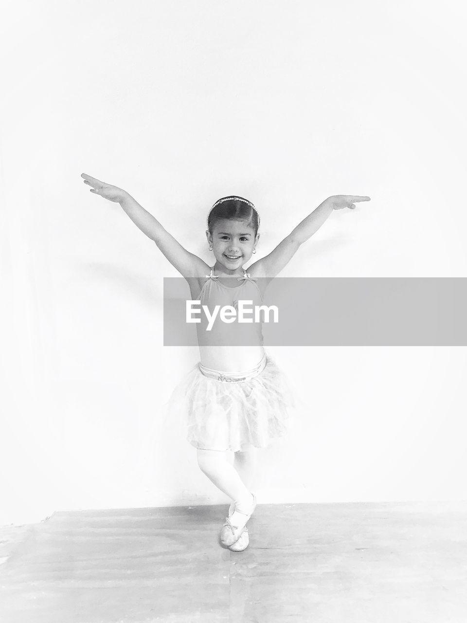 Portrait Of Smiling Girl Doing Ballet Dance Against Wall
