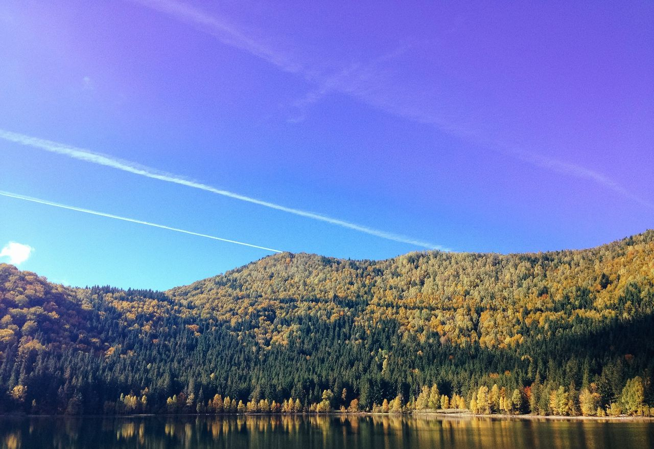 sky, vapor trail, beauty in nature, tranquility, scenics - nature, tranquil scene, plant, water, nature, tree, no people, lake, day, blue, mountain, waterfront, non-urban scene, idyllic, clear sky, outdoors
