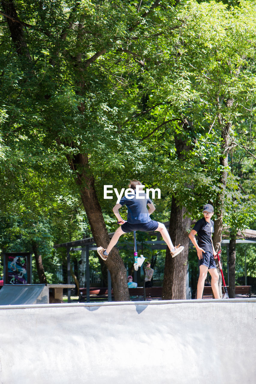tree, plant, full length, real people, leisure activity, sport, lifestyles, casual clothing, day, nature, men, people, growth, motion, transportation, child, outdoors, green color, childhood, rear view, riding
