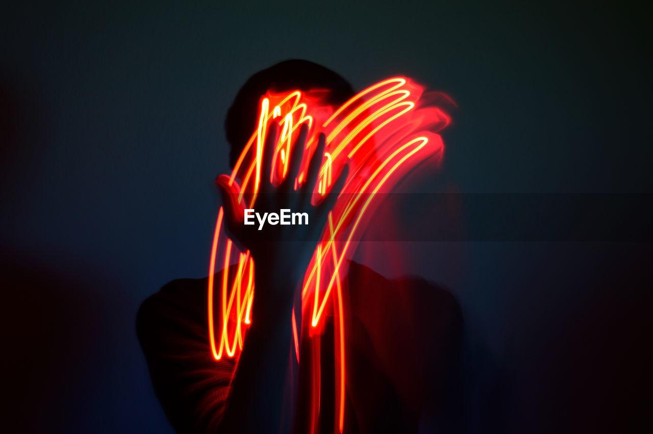 Digital composite image of light painting against black background