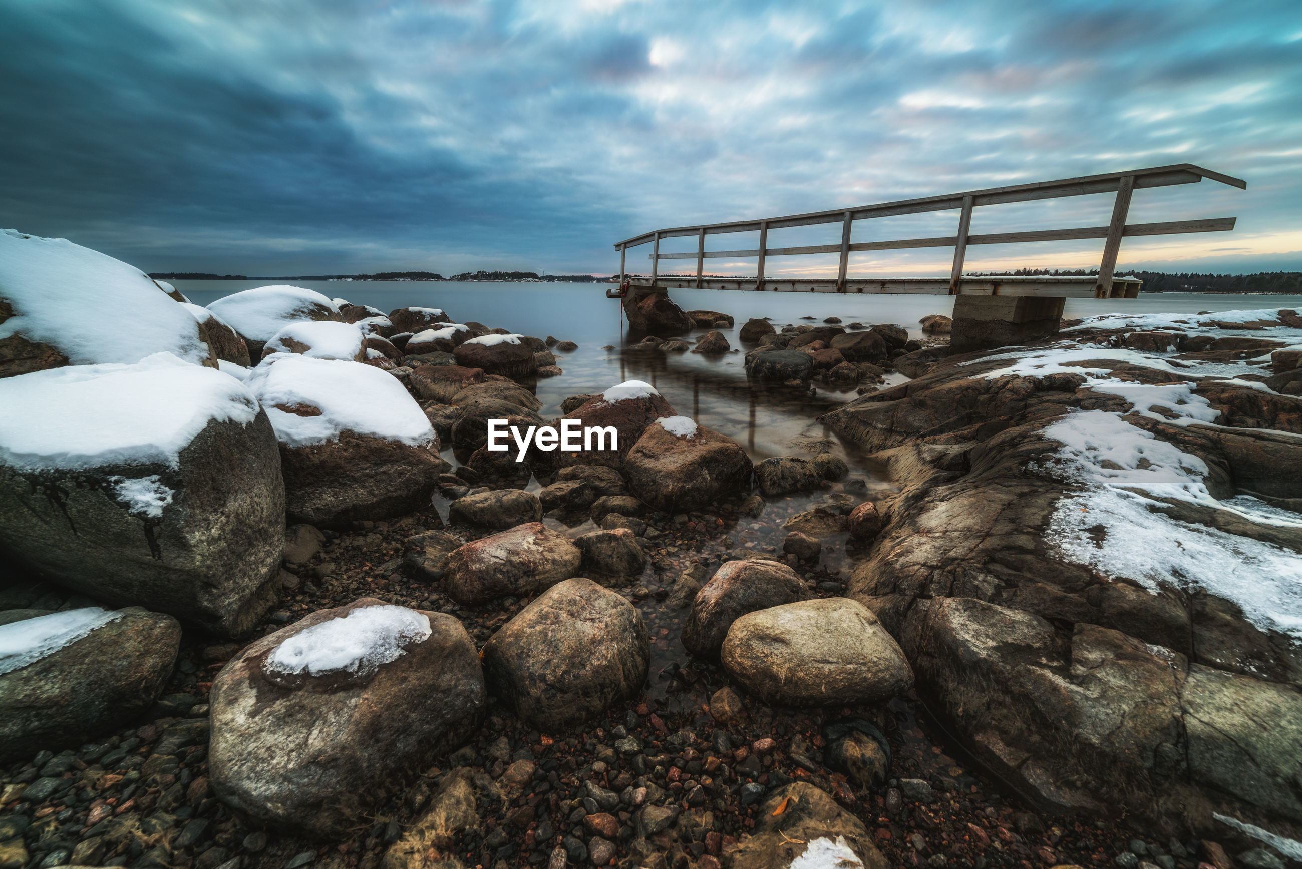 Railing on rocky coastline against cloudy sky during winter