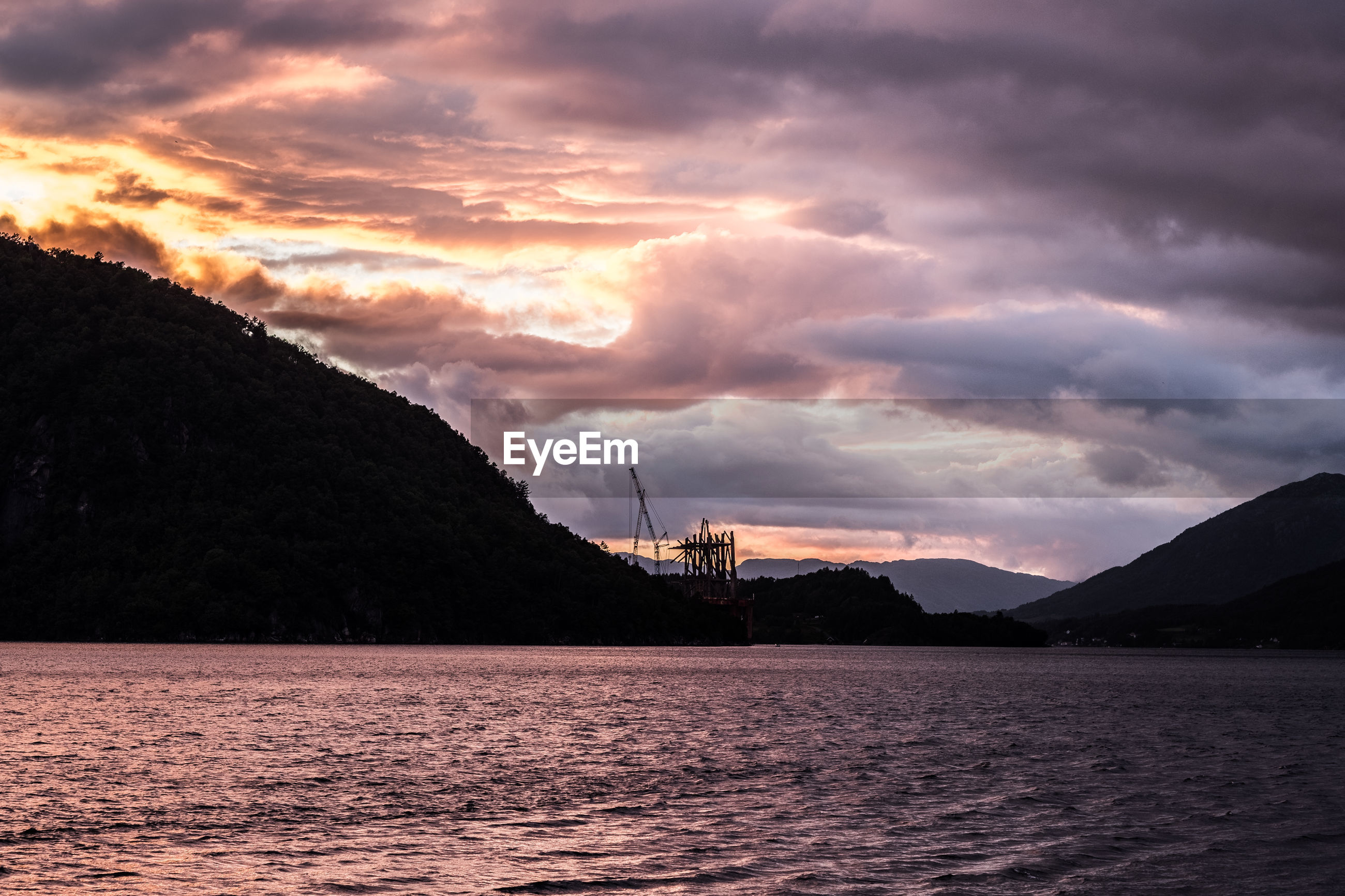 SCENIC VIEW OF DRAMATIC SKY OVER SEA AND MOUNTAINS