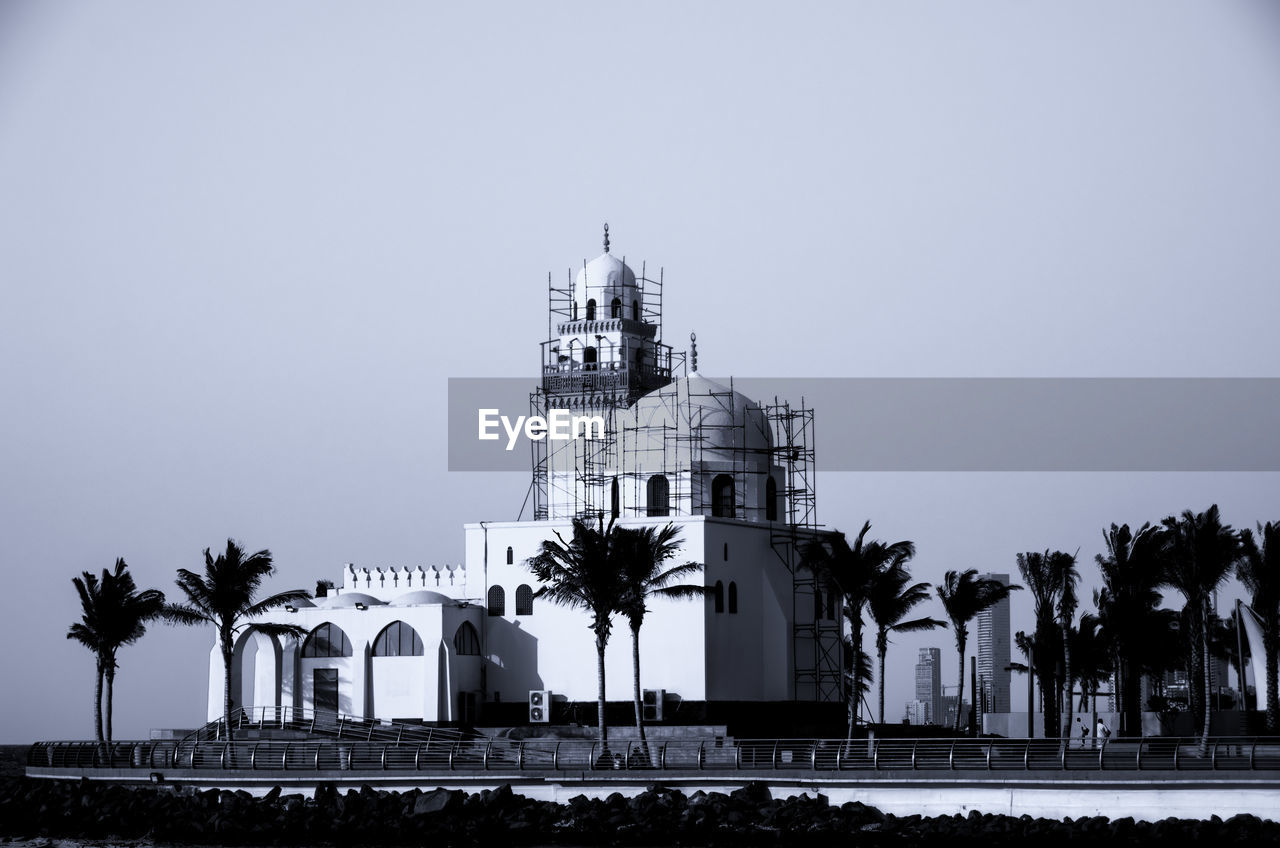 building exterior, built structure, sky, architecture, tree, palm tree, building, nature, place of worship, tropical climate, clear sky, religion, copy space, belief, spirituality, plant, travel destinations, no people, city, outdoors, spire
