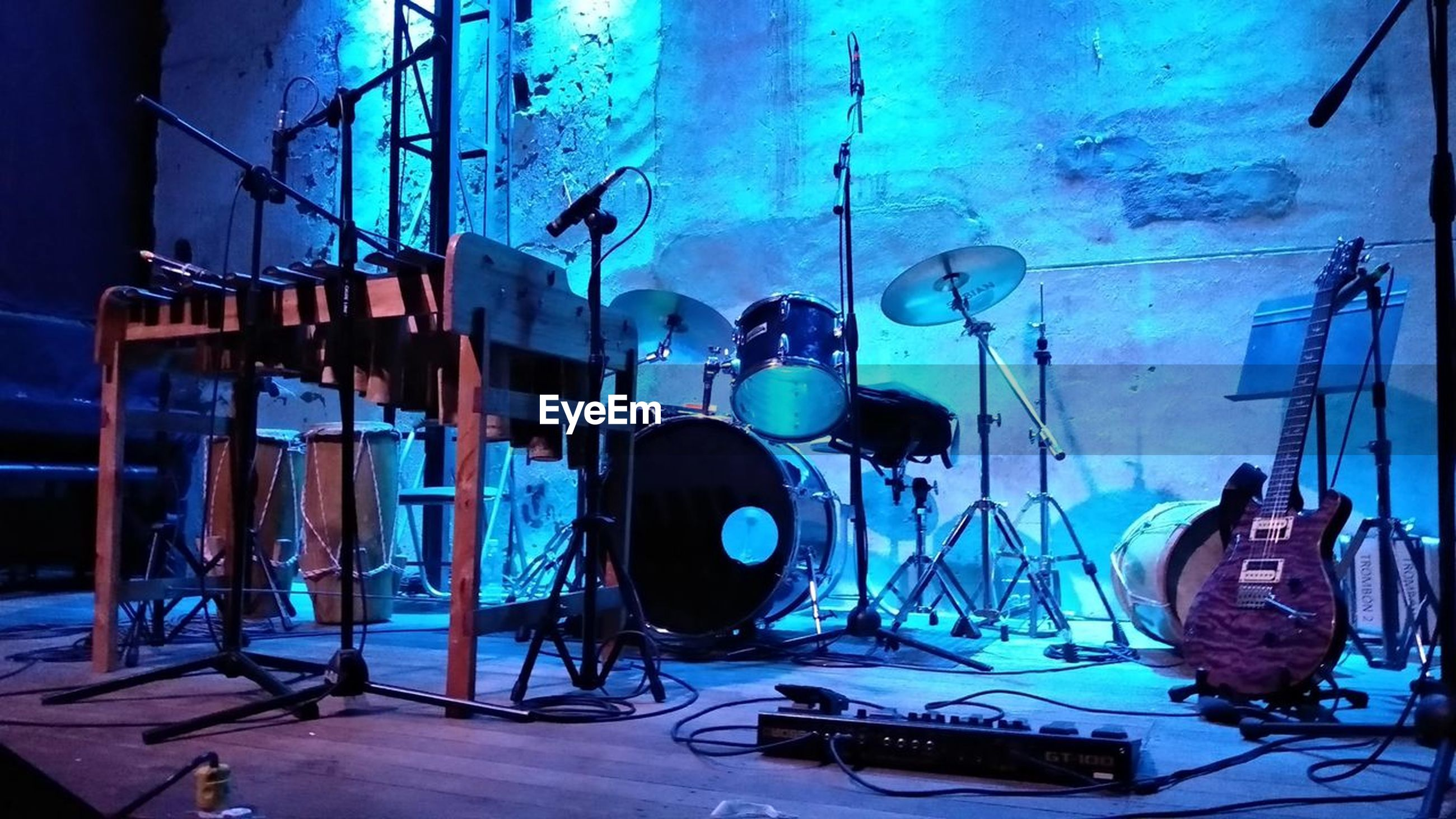 music, musical instrument, arts culture and entertainment, musical equipment, indoors, string instrument, microphone, input device, guitar, no people, drum kit, blue, drum, audio equipment, equipment, performance, stage, rock music, drum - percussion instrument, stage - performance space, nightlife